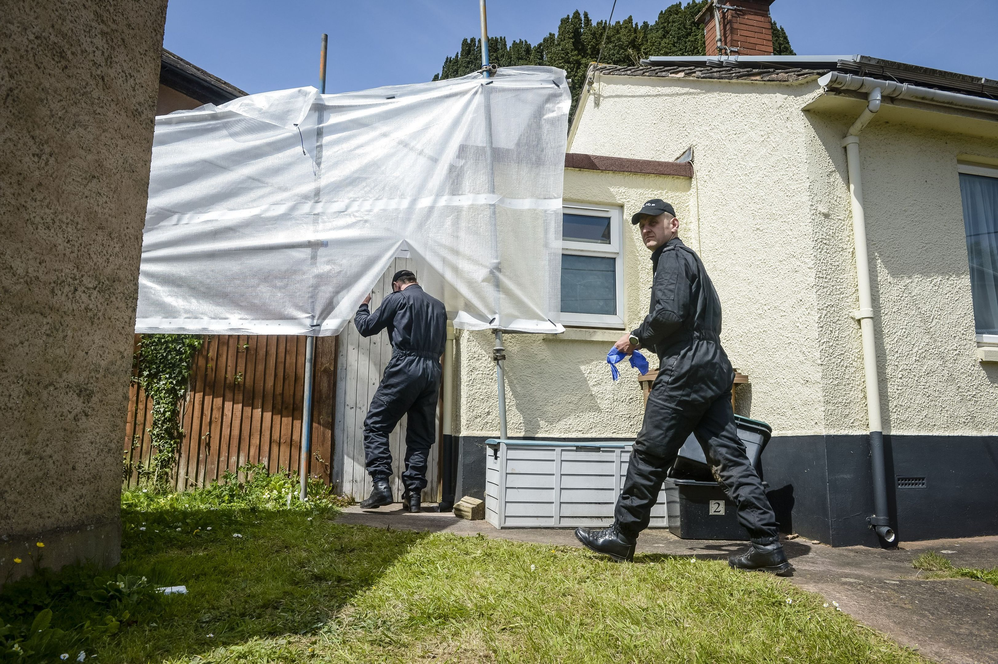 Police enter the tarpaulin covered garden at the couple's former home.