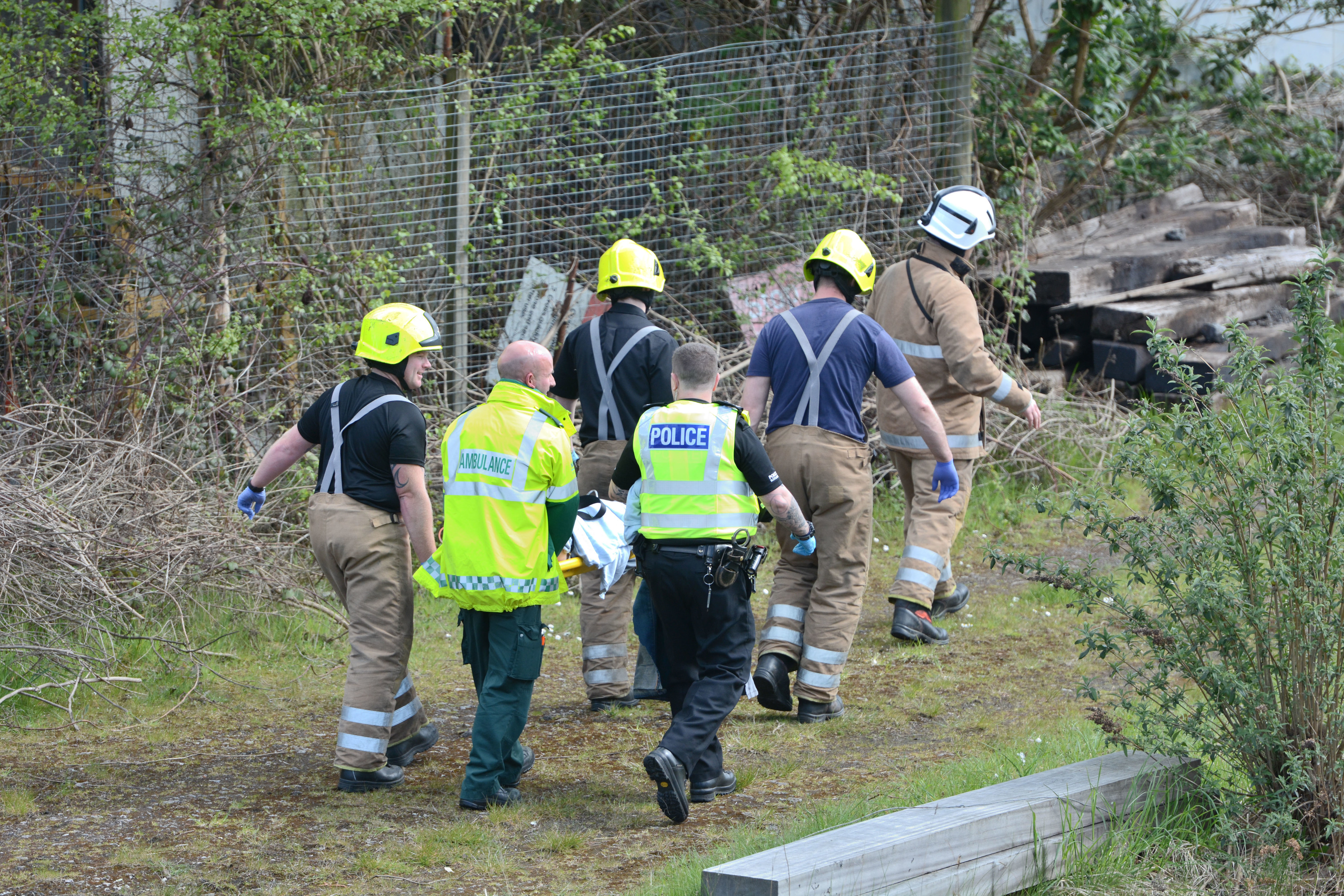 The injured man is led away after accident at Perth railway line.