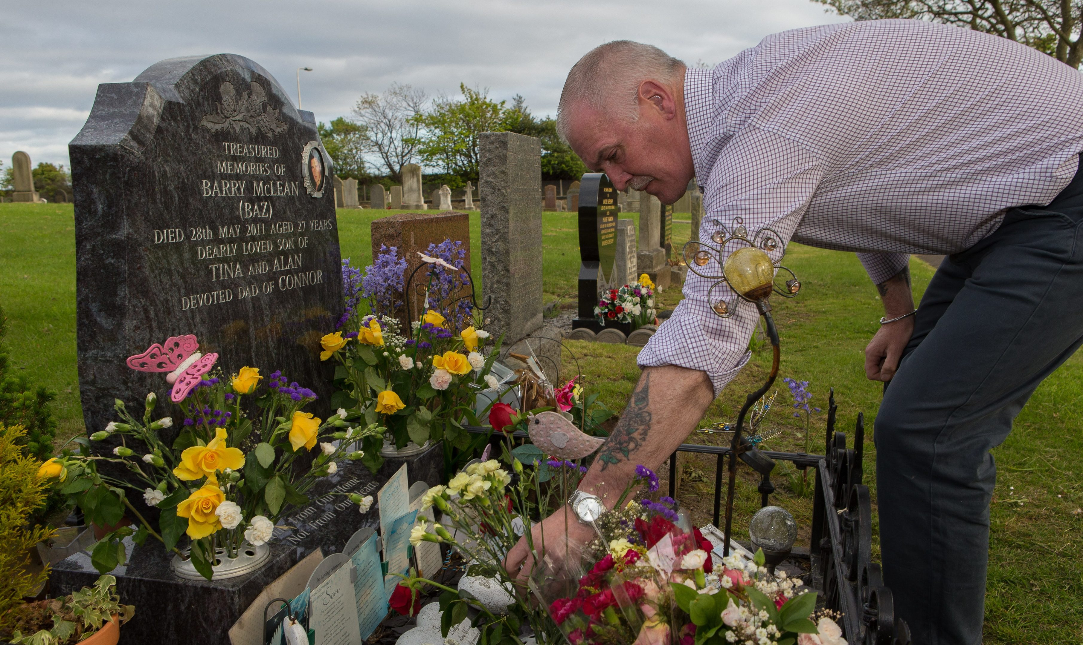 Alan McLean tends the grave of his son Barry McLean who died after a knife attack on May 28, 2011.