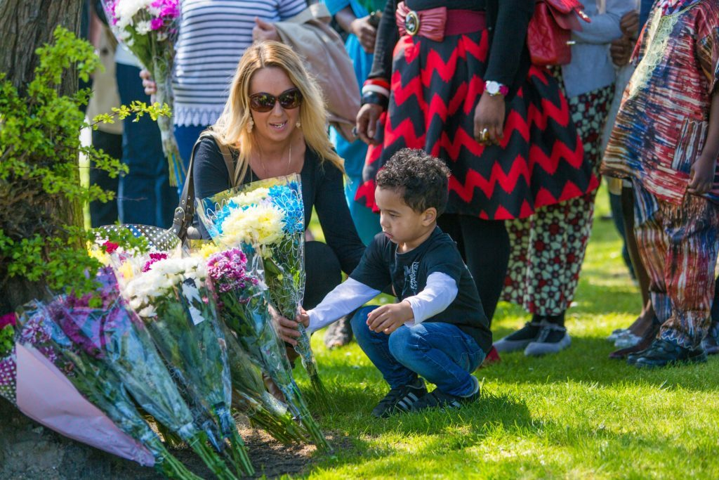 Friends and Family members pay tribute on the anniversary of the death of Sheku Bayoh who died in Police Custody. Together with family lawyer Aamar Anwar, the family laid flowers at the site of his death before meeting in Templehall Community Centre in Kirkcaldy. Sheku's son lays flowers with help from a family member