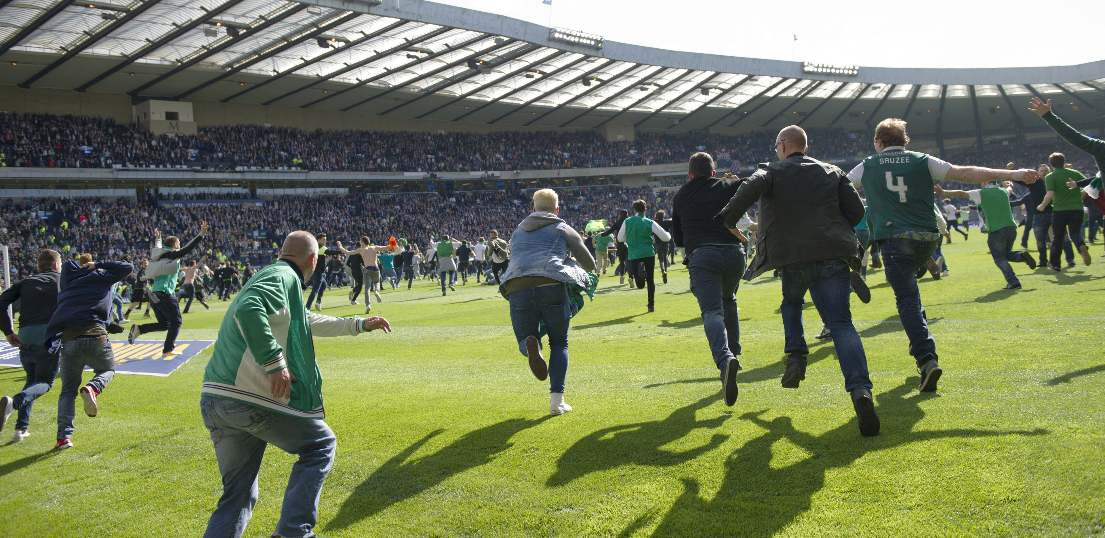 Hibernian fans rush the pitch after their side's win in the Scottish Cup final.