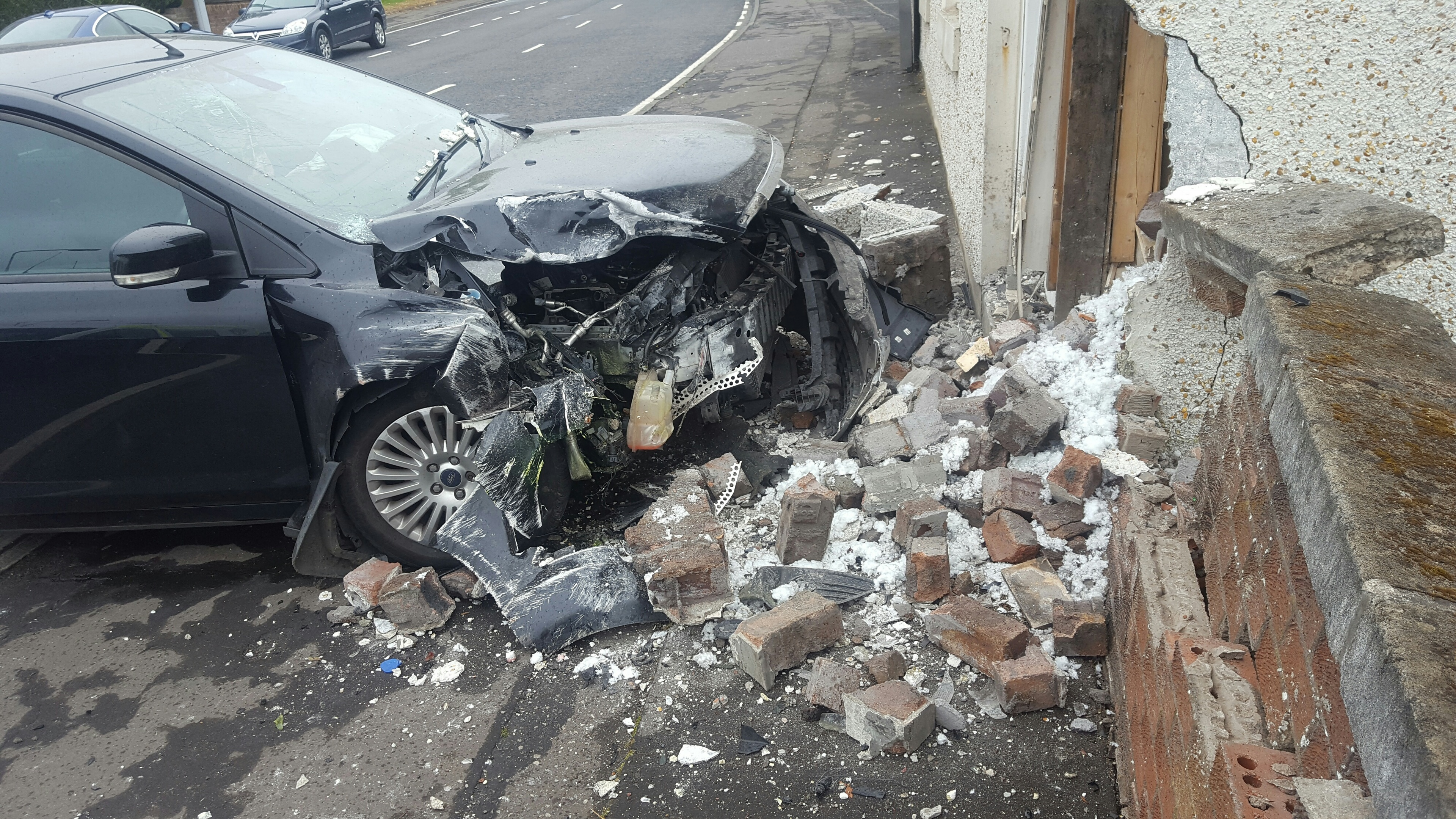 The badly damaged car lies amid the rubble after the impact.