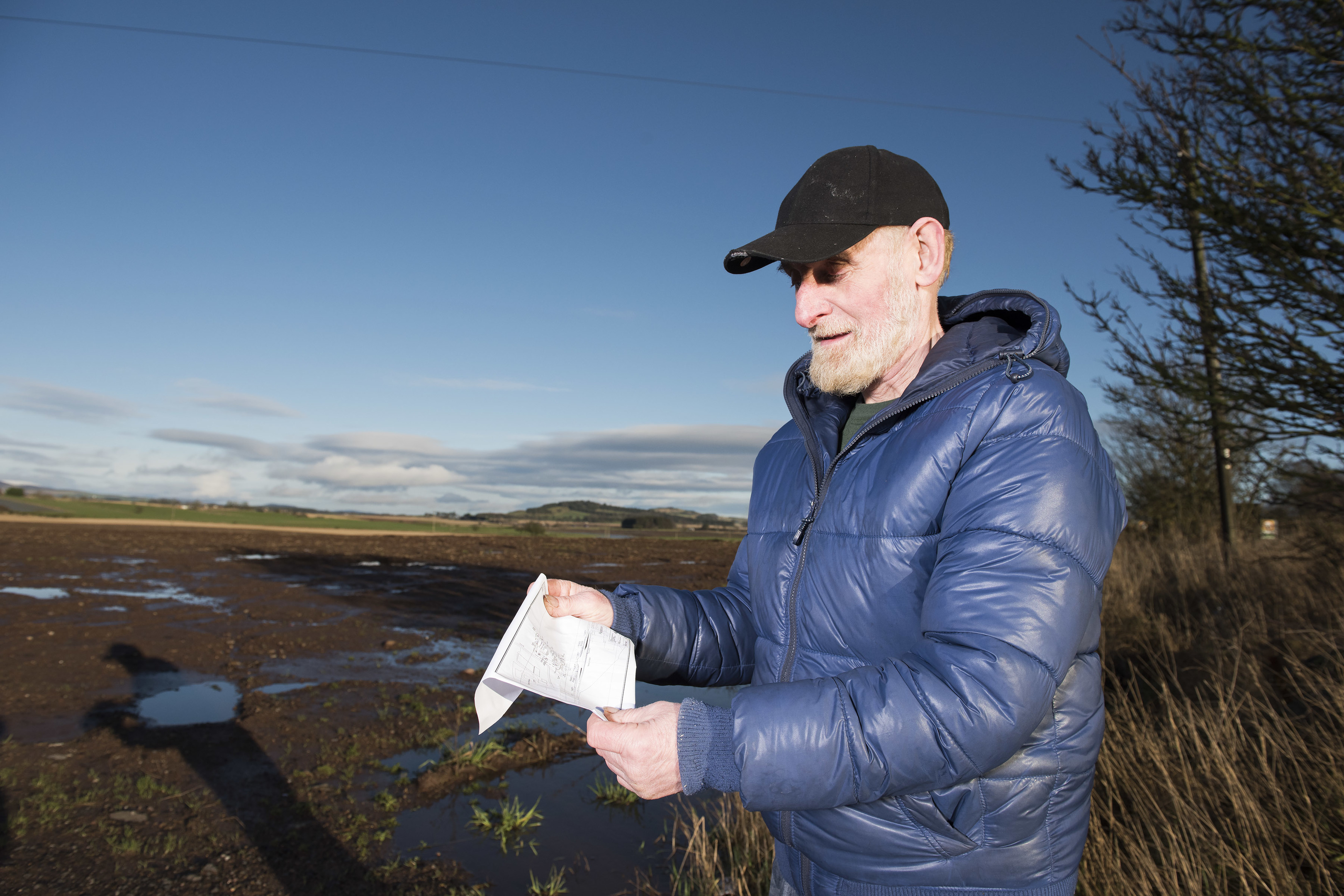 Resident Frank Morrison looks at a copy of the plans for a new recycling centre at Padanaram.