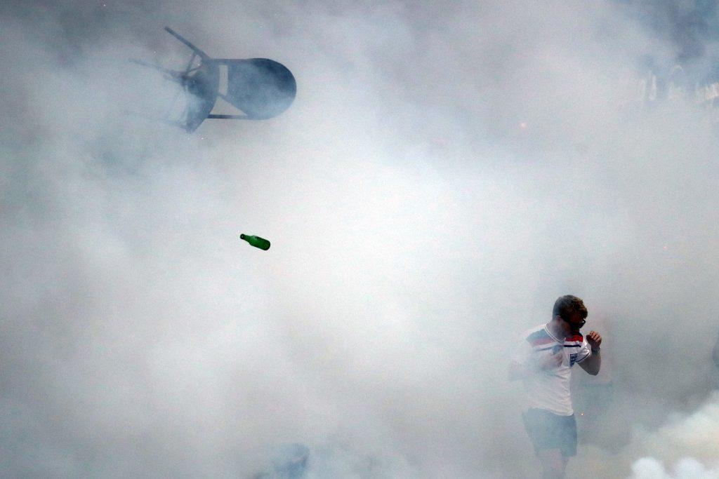 A bottle and chair are thrown as an England fan walks through tear gas.