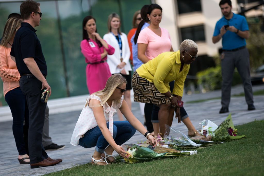 People lay flowers at the Dr. Phillips Center for the Performing Arts in honor of the victims of the shooting at Pulse Nightclub.