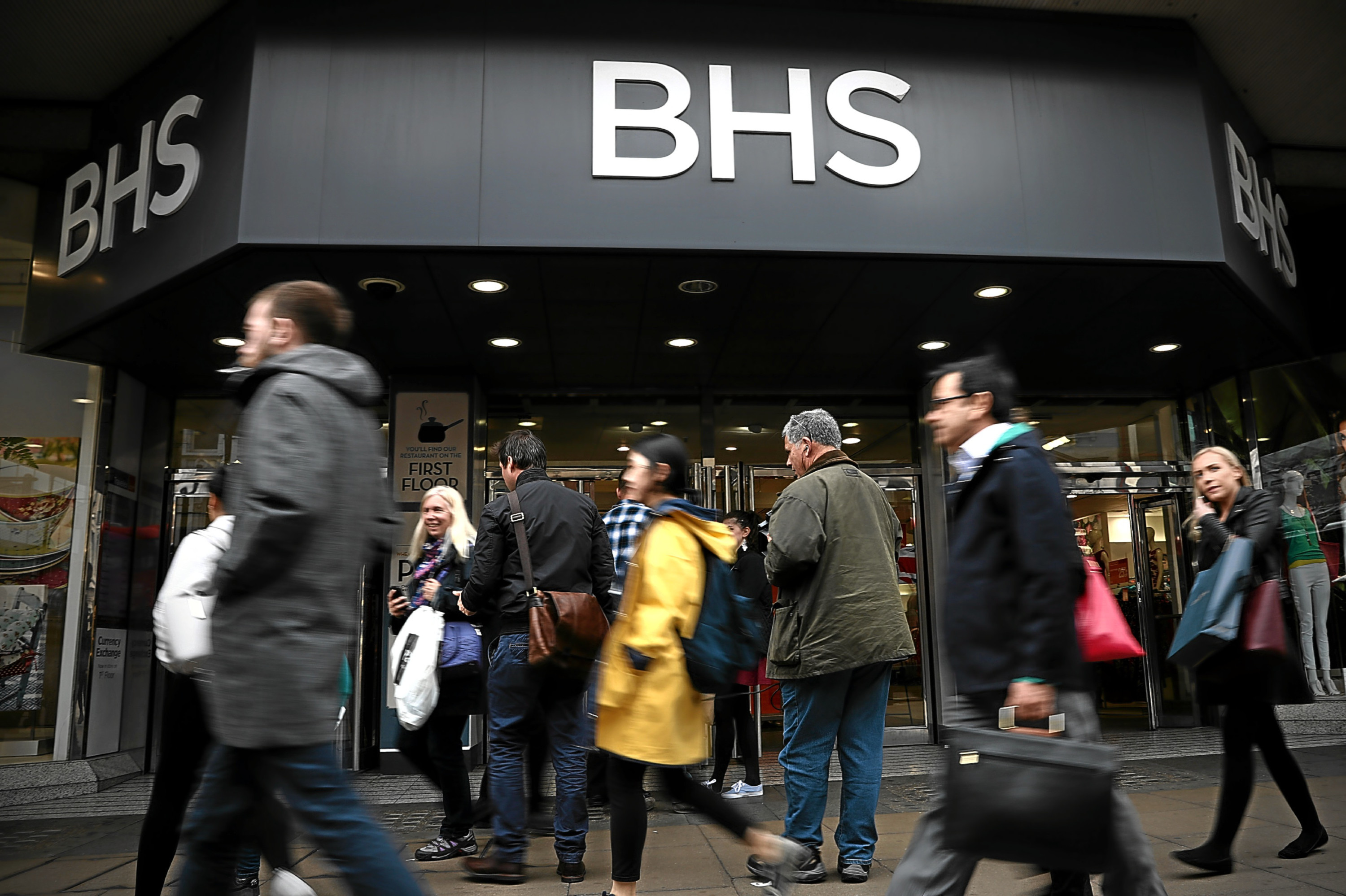 People walk past a branch of British Home Stores