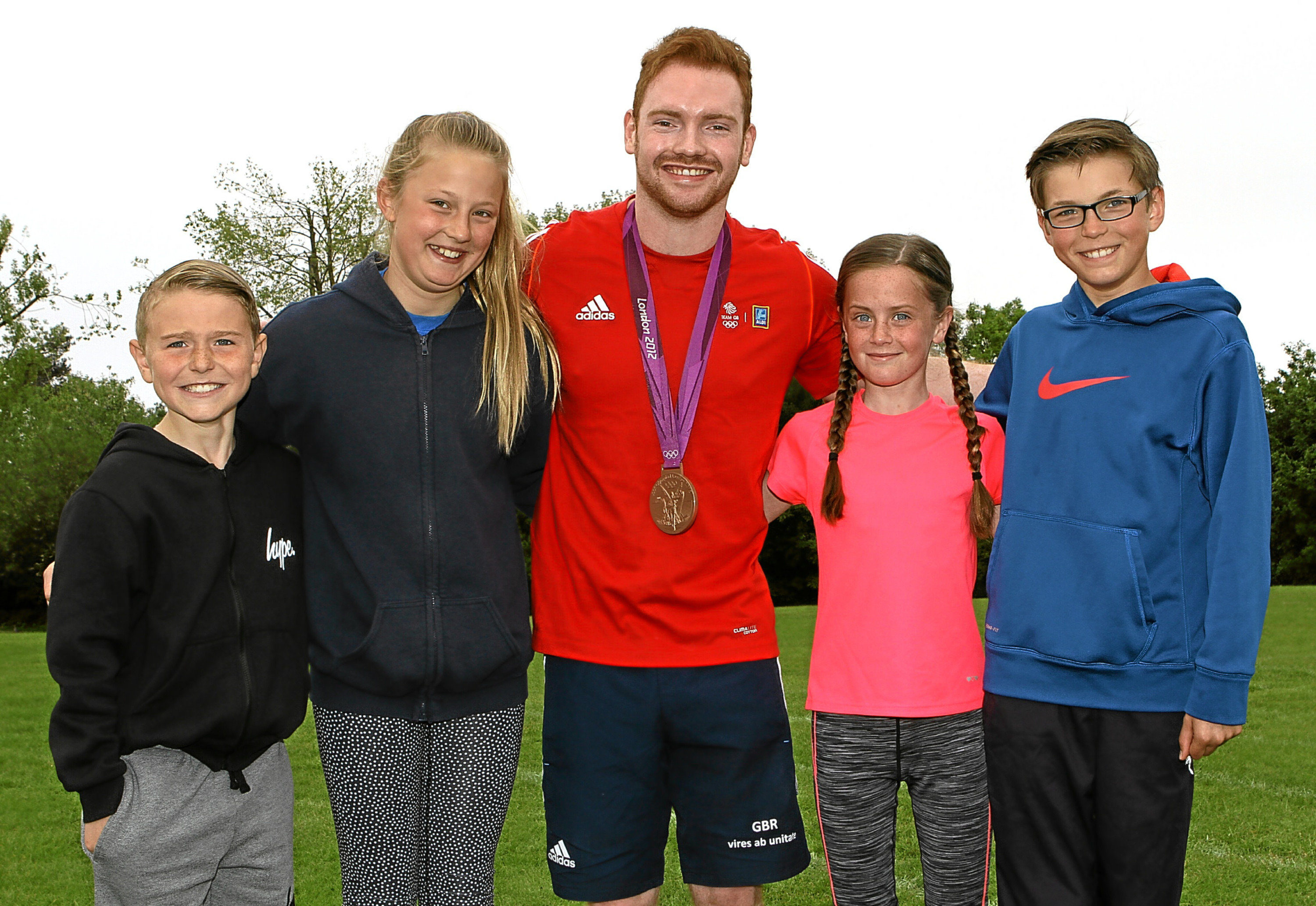 COURIER, DOUGIE NICOLSON, 06/06/16, NEWS. TEAM GB GYMNAST DAN PURVIS AT GRANGE PS. Pictured at Grange Primary School in Monifieth today, Monday 6th June 2016, is Team GB Gymnast, Dan Purvis with L/R, Aidan Cobb, Niamh Grogan, Beverley Kydd and Lewis Grant, all P6. Story by Angus office.