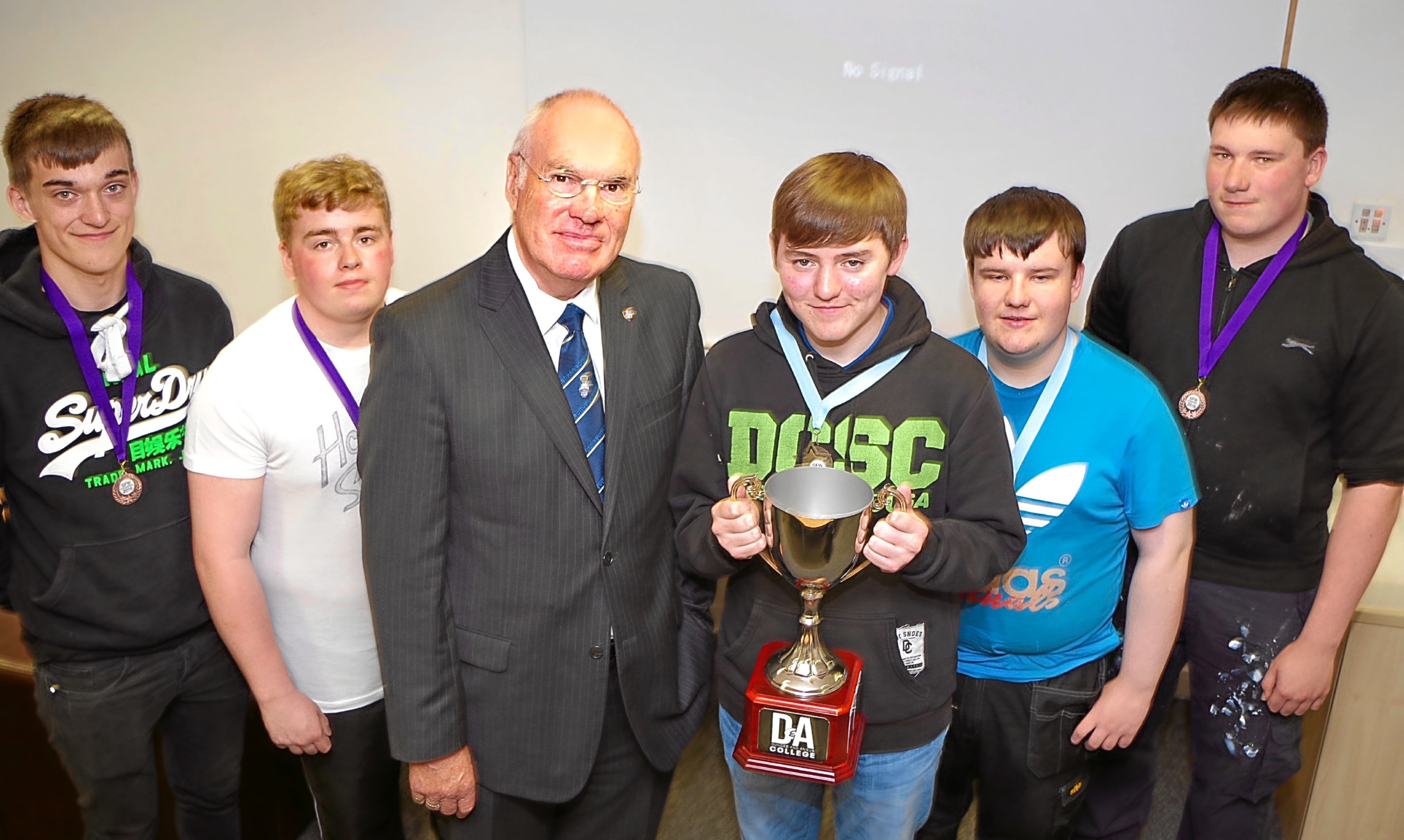 Deacon convenor of the Nine Trades of Dundee, Murray Petrie, presents John McCafferty with the trophy for winning a construction skills contest at D&A College, Arbroath Campus. Looking on are competition finalists, from left - Jenson Pye, Lee Robertson, Andrew Kinnear and Fraser MacIntosh.