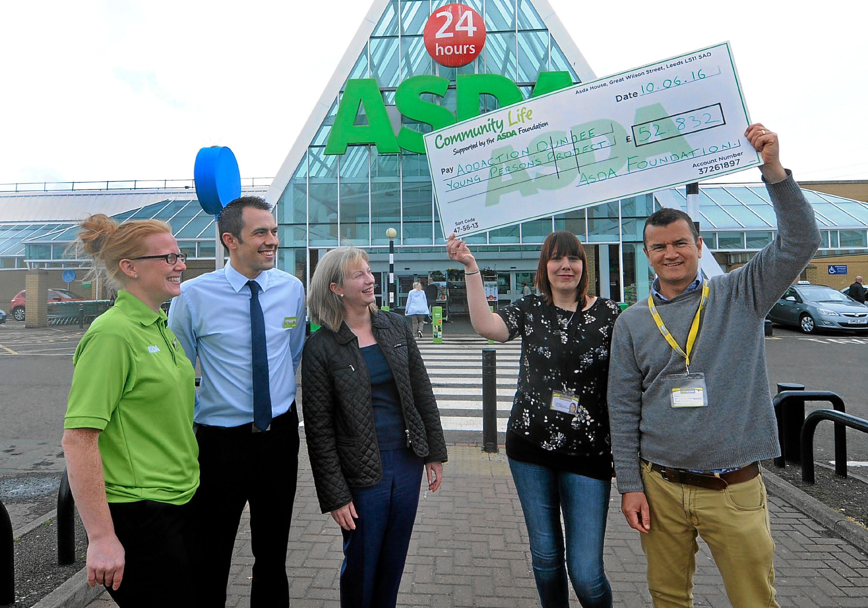 Asda's Yvanne McLaren and Craig Fisher and MSP Shona Robison look on as Alain Saum and Dave Barry of Young Addaction, Dundee hold up the cheque.