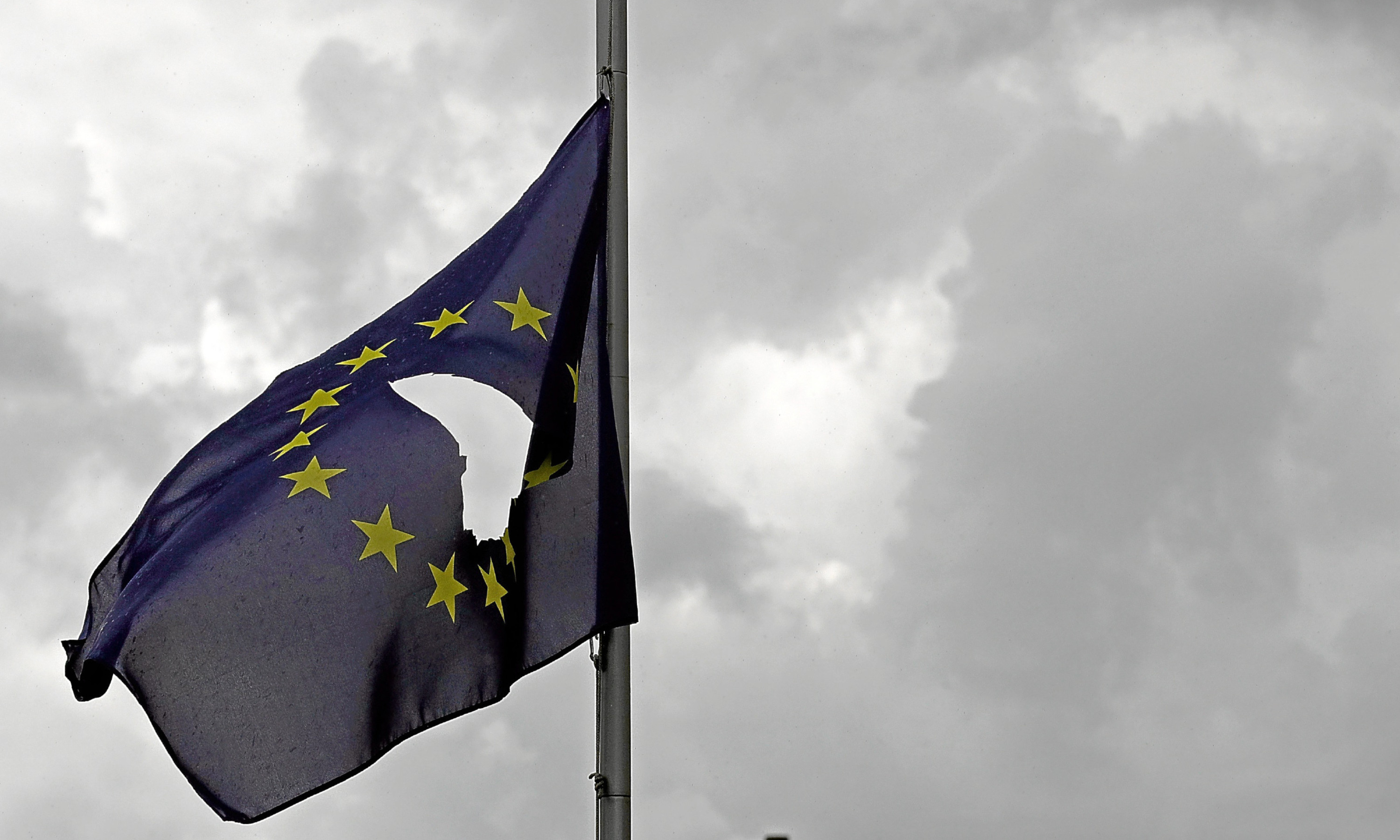 A European Union flag, with a hole cut in the middle, flies at half mast.