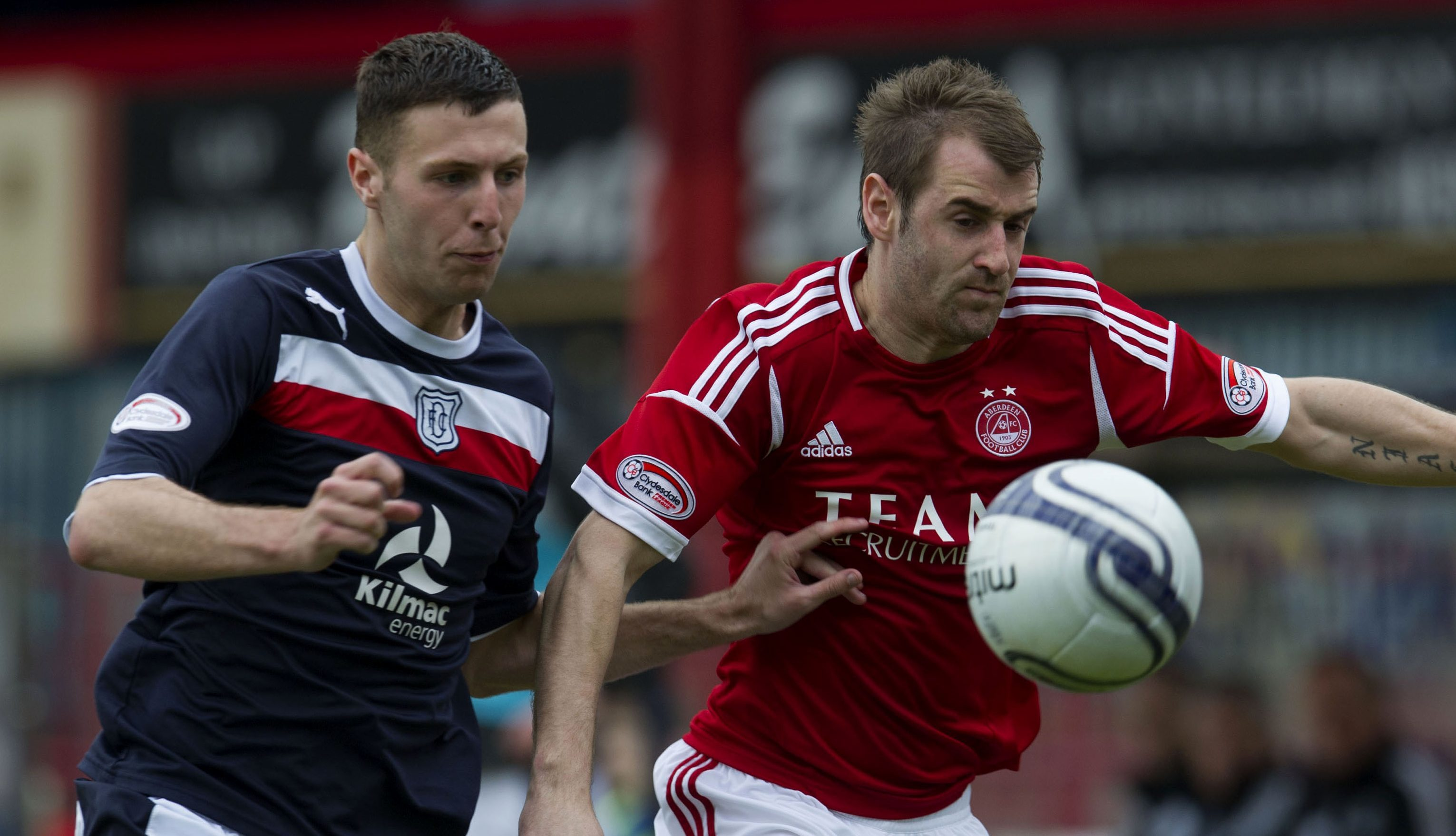 Lewis Toshney in action for Dundee against Aberdeen's Niall McGinn.