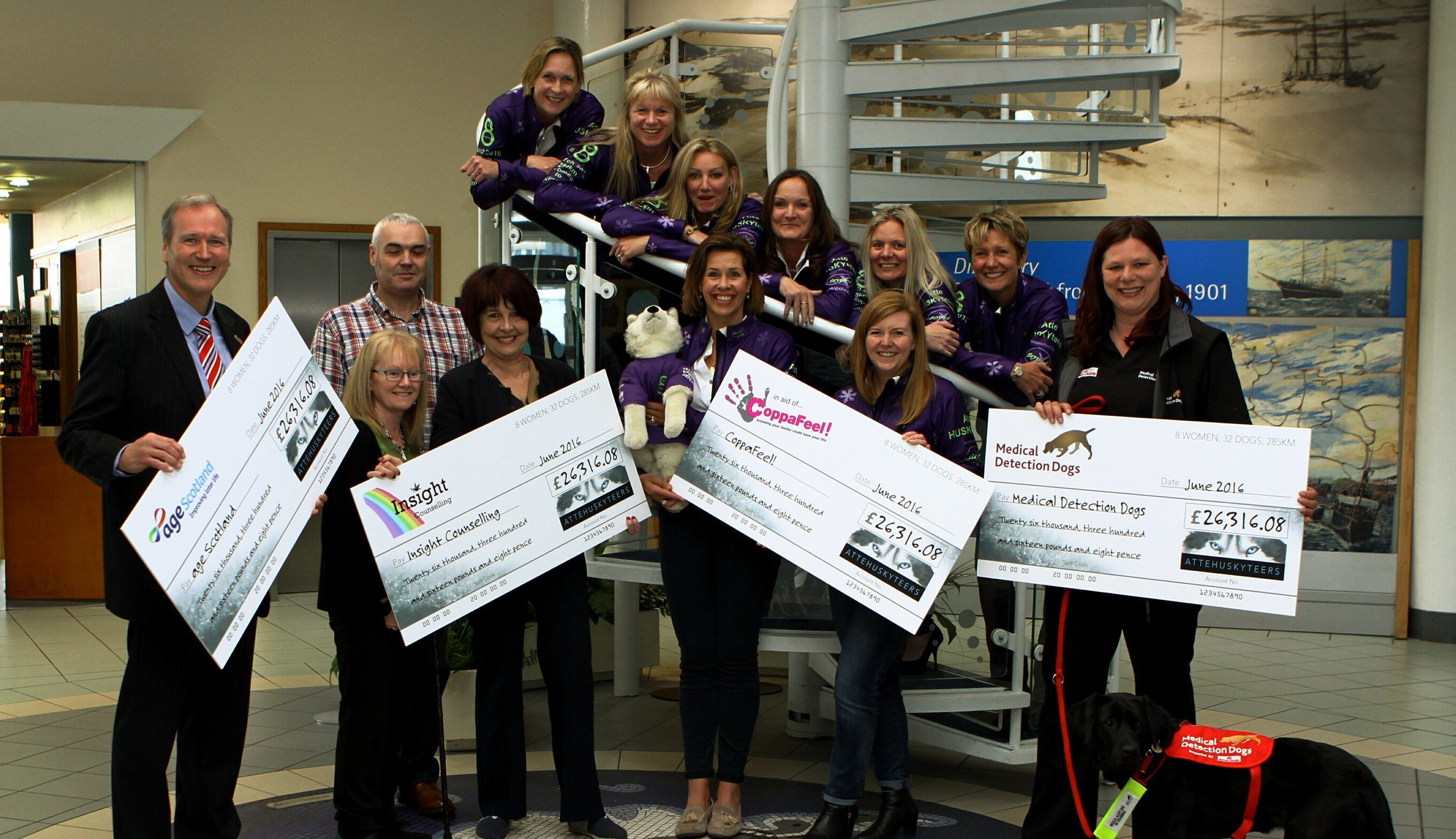 The Huskyteers hand their cheques to four charities
