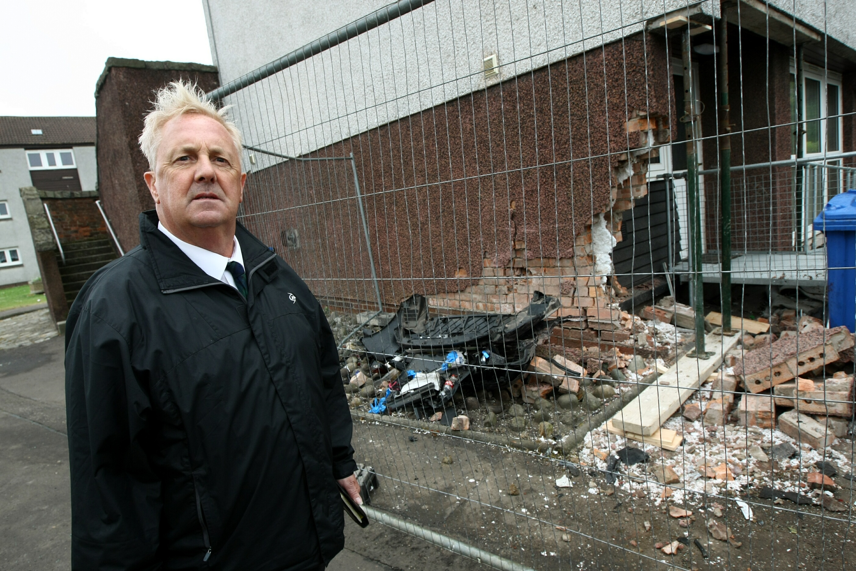 Councillor John O'Brien surveys damage to flats after a car crash in Methil.
