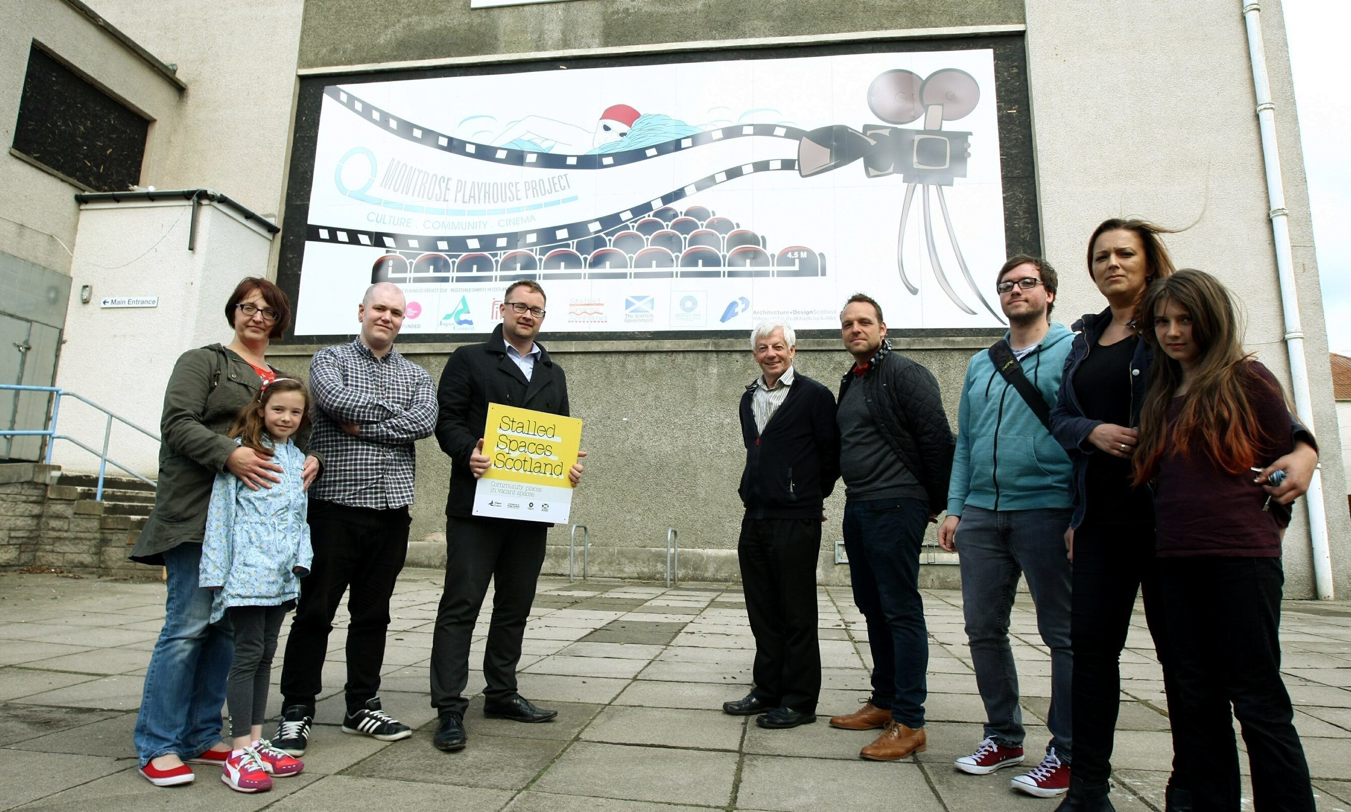 Playhouse project secretary Wendy Ellis with her daughter Maisie, Kyle Stokes of Dundee and Angus College, project chairman David Paton, Councillor David May, Mark Ruxton of Keillor Graphics, Andy Carlisle of Dundee and Angus College and Magda Garas with her daughter Ola in front of the banner.