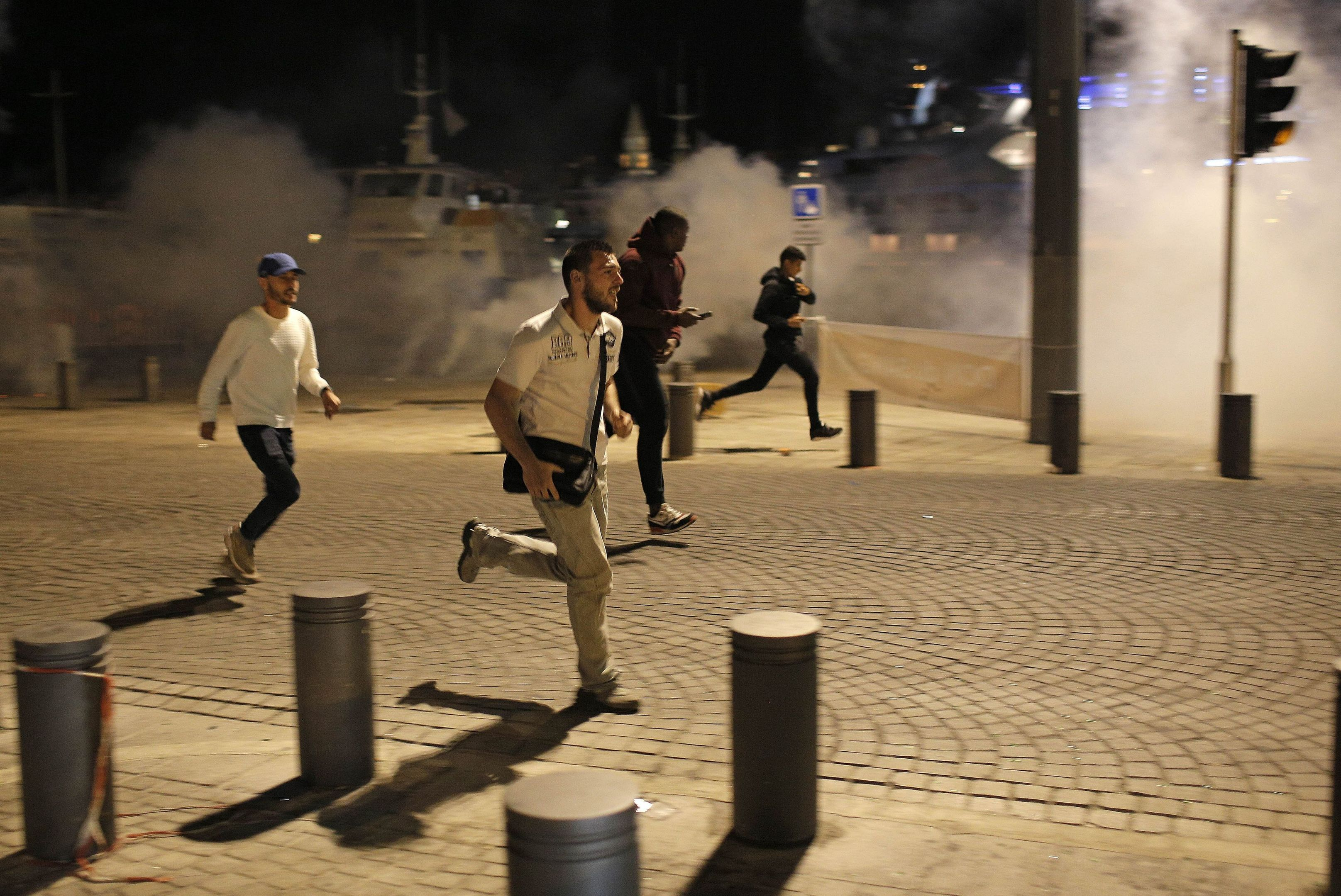 People run through the streets of Marseille after police fired tear gas following the match between England and Russia.
