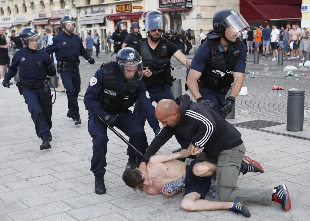 A man is apprehended by French police in downtown Marseille, France, Friday, June 10, 2016. Some minor scuffles on Friday and the brief clashes late Thursday revived bitter memories of days of bloody fighting in this Mediterranean port city between England hooligans, Tunisia fans and locals of North African origin during the World Cup in 1998, and raised fears of more violence ahead of Saturday's European Championship match between England and Russia at the Stade Velodrome. (AP Photo/Darko Bandic)
