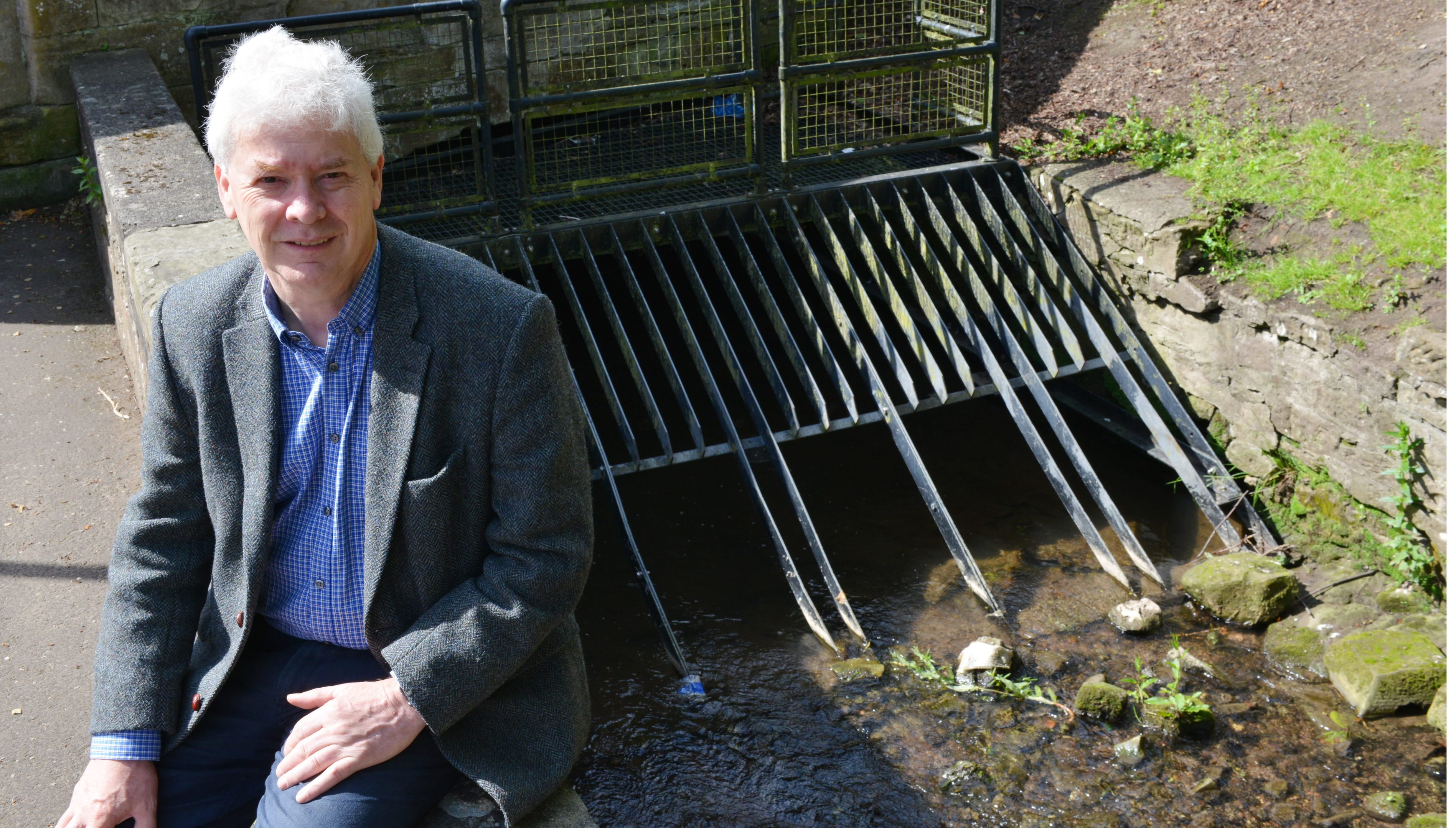 Councillor Bryan Poole  at  the Lady Burn in Cupar, which is prone to flooding