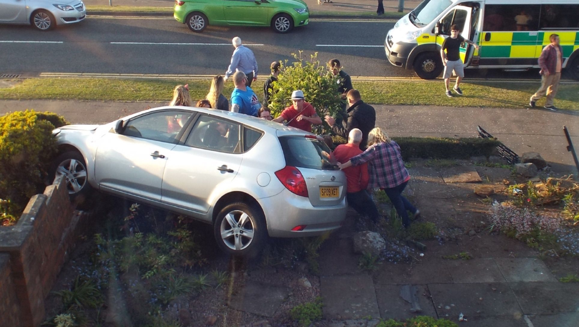 Neighbours help right the car which crashed into a garden in South Parks Road, Glenrothes