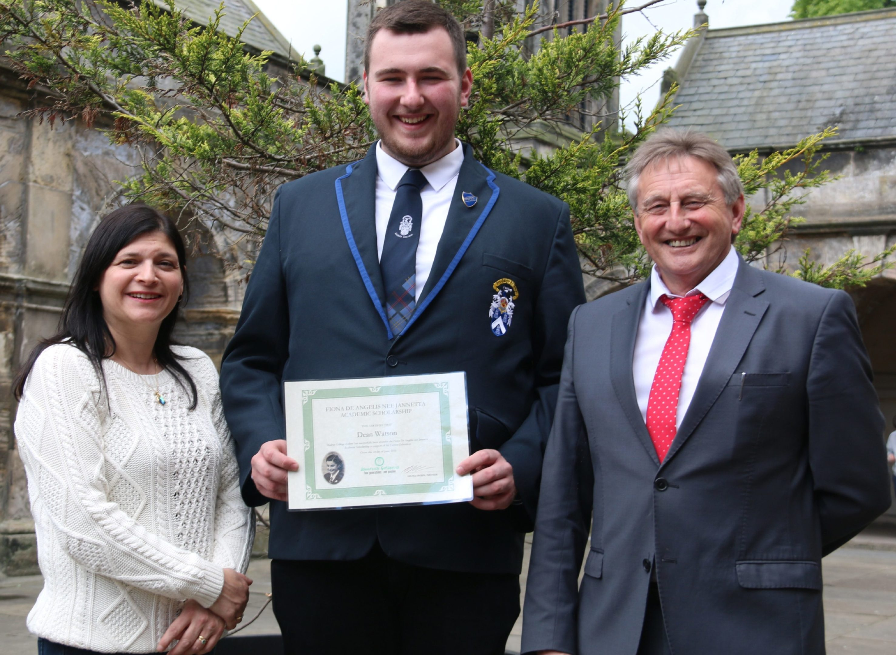 Dean Watson receiving the scholarship certificate from Nicola Hazel, in the presence of Madras Rector David McClure.