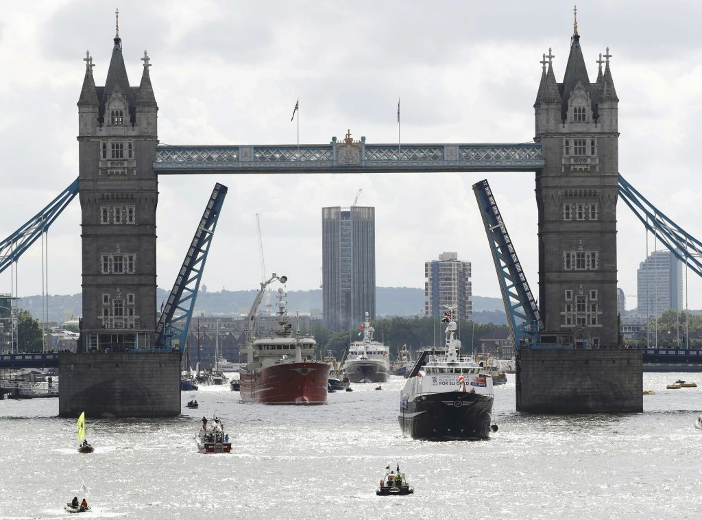 """A pro-Remain inflatable dinghy sails alongside a Fishing for Leave pro-Brexit """"flotilla"""" making its way under Tower Bridge."""