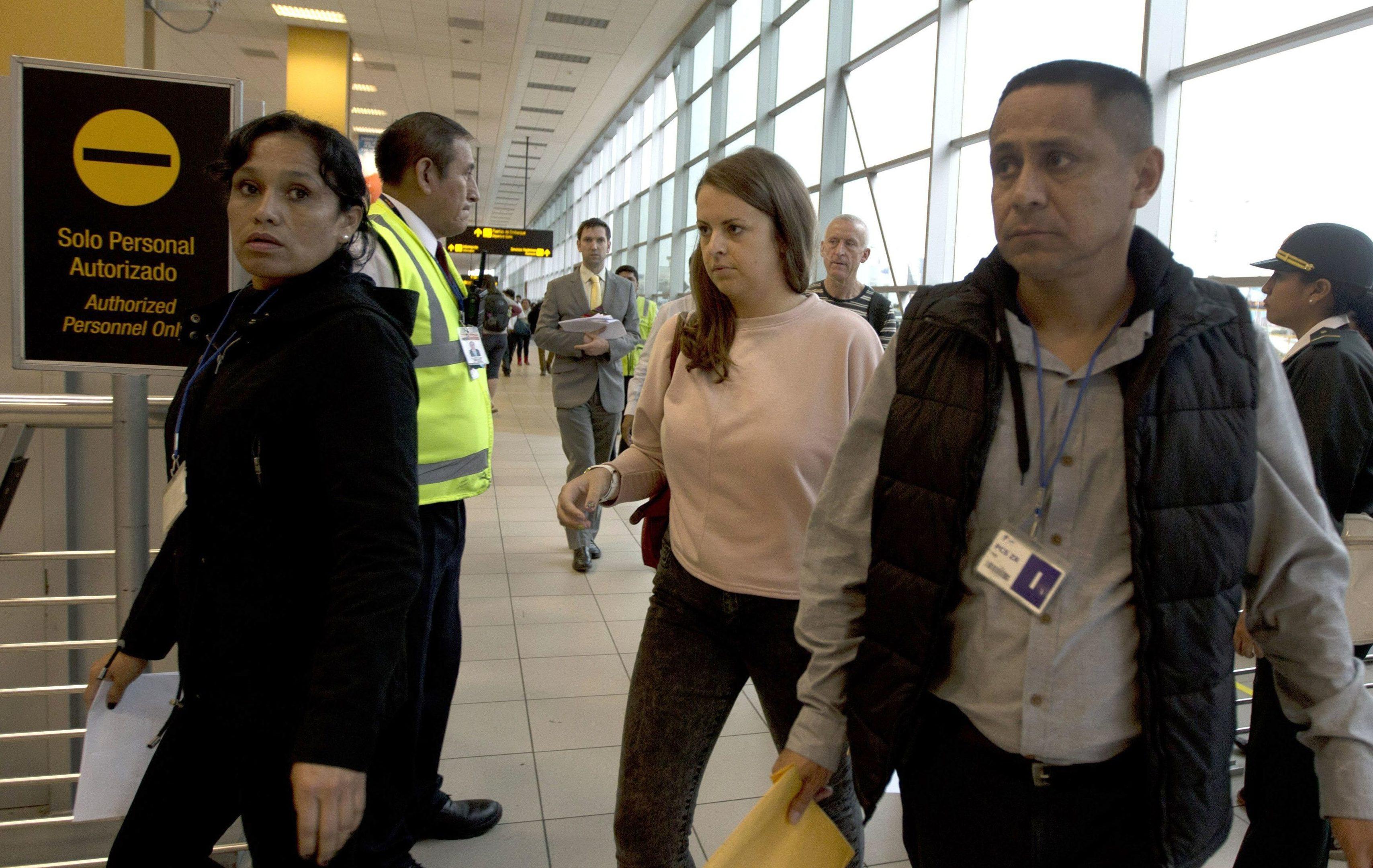 Melissa Reid, centre, boards a flight home from Lima, Peru.