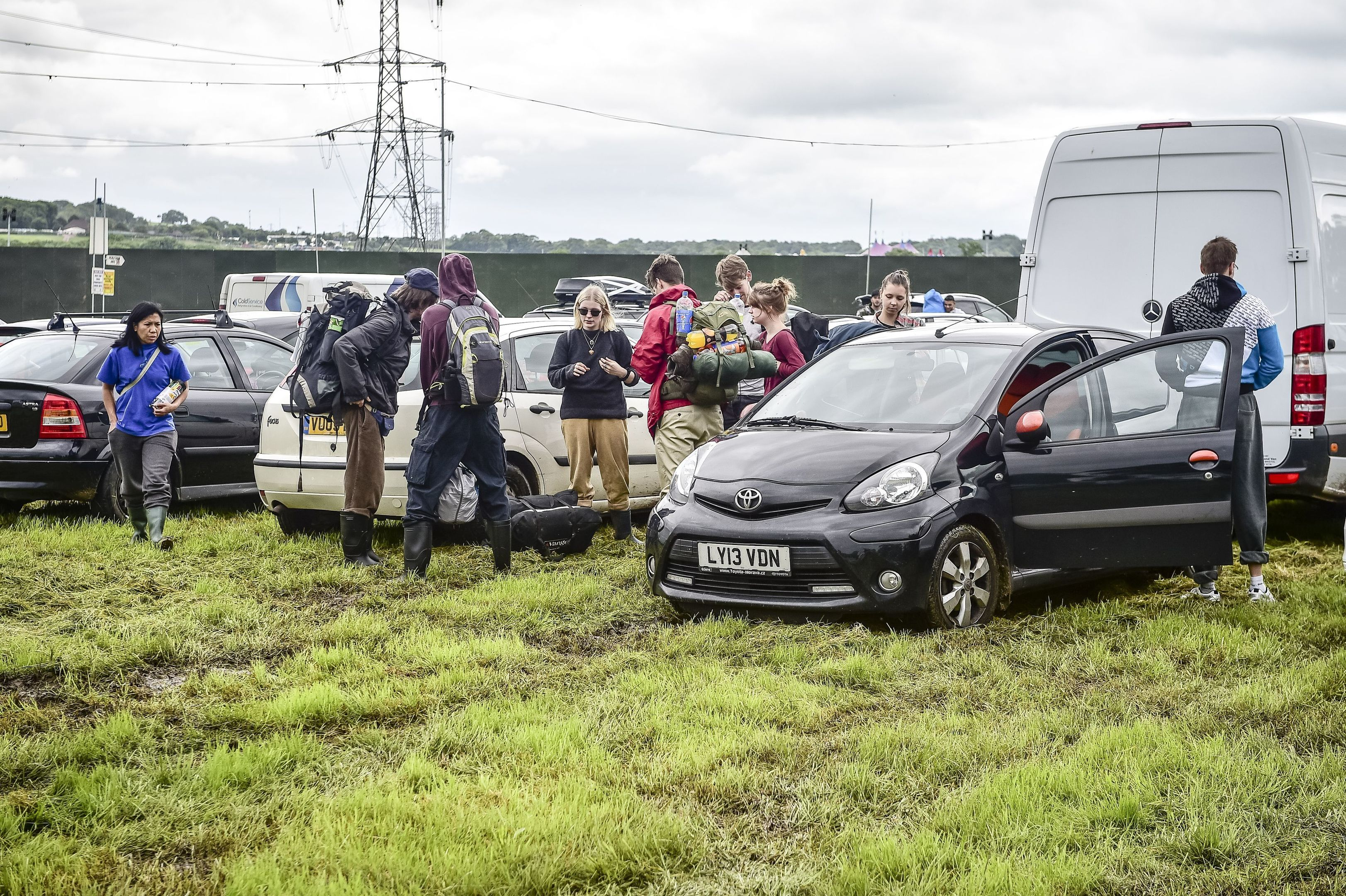 People arrive and park in muddy and waterlogged fields at Glastonbury festival.