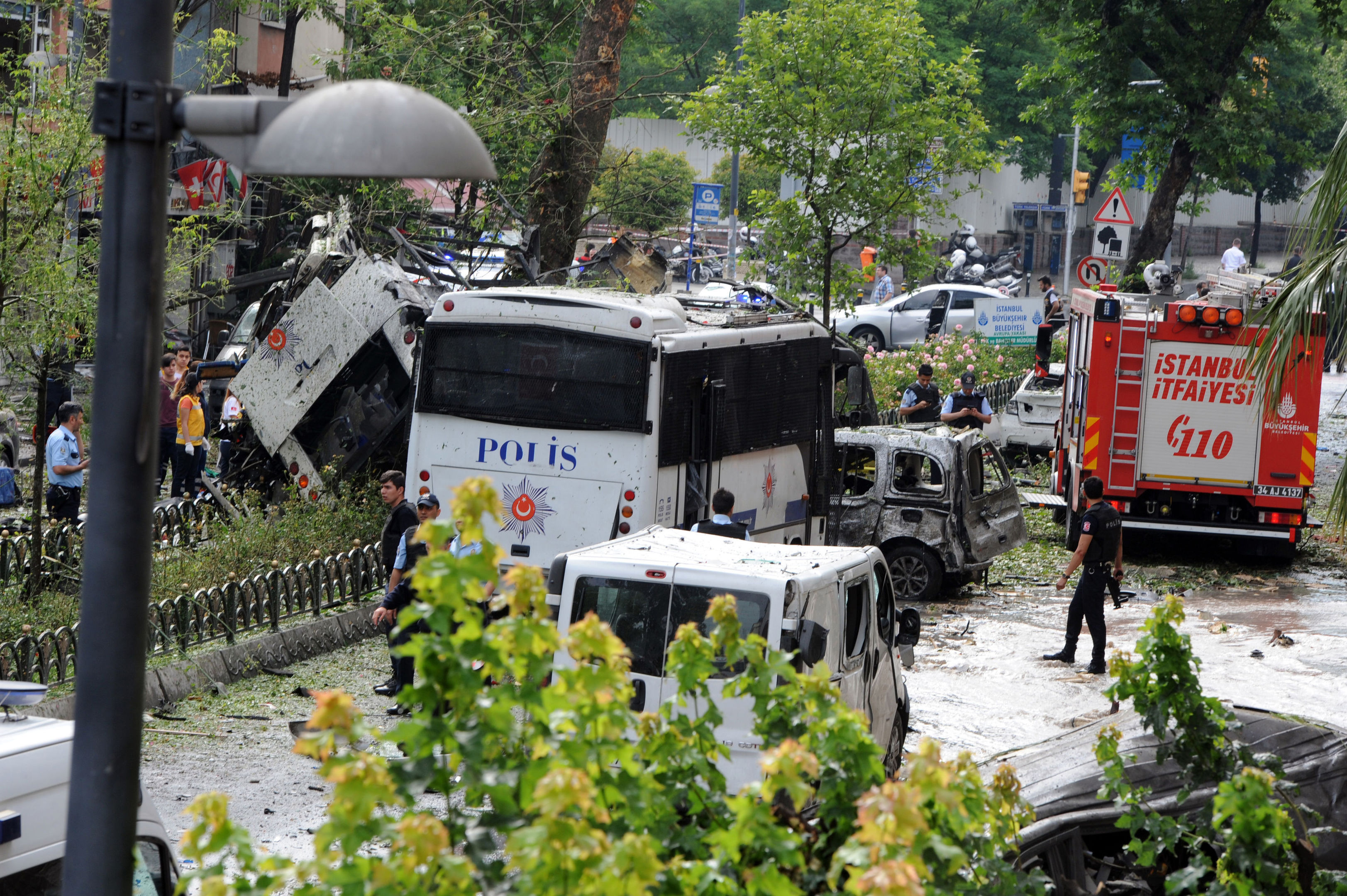 Turkish security officials and firefighters work at the explosion site after a bus carrying riot police was struck by a bomb in Istanbul.