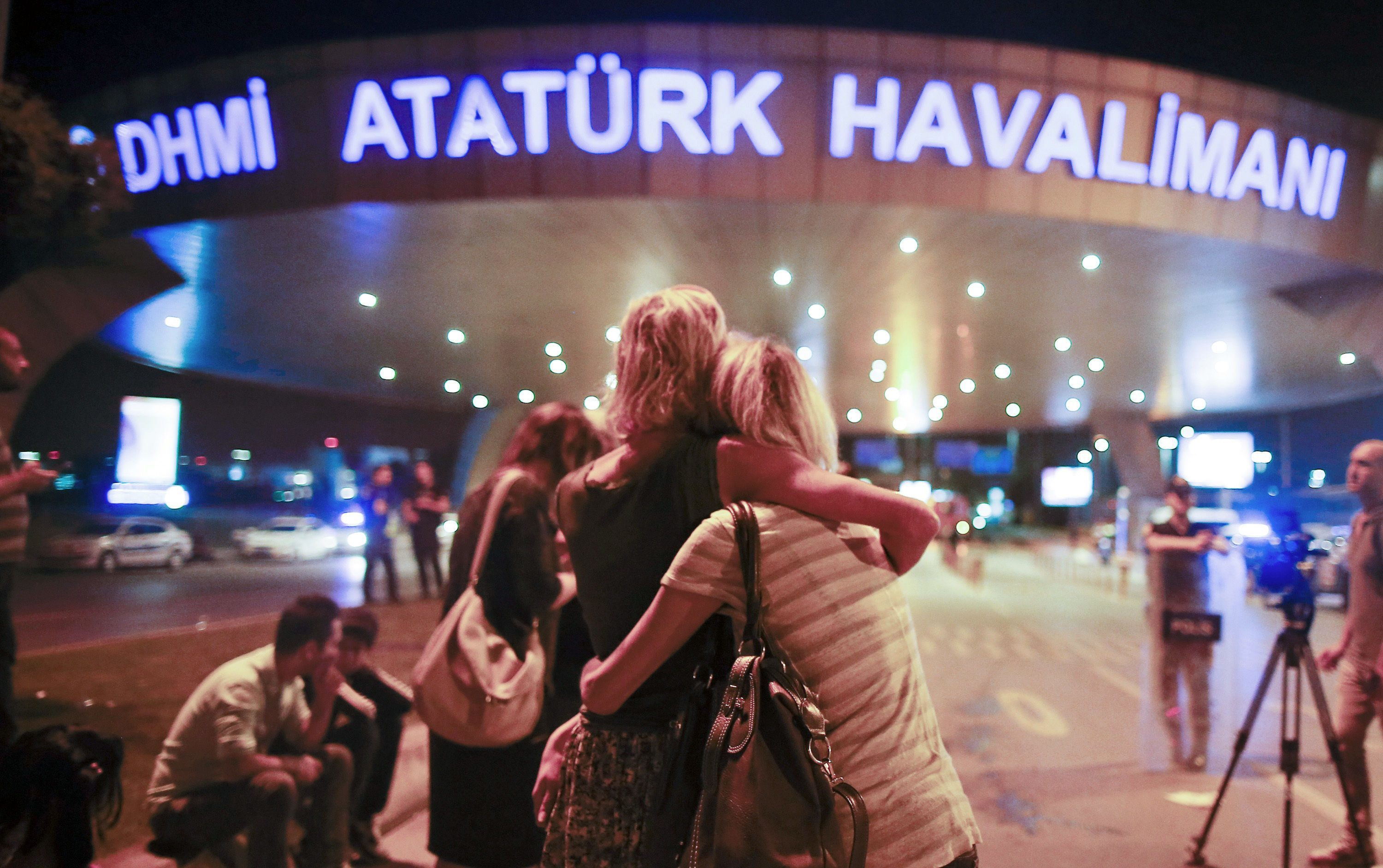 Passengers embrace each other at the entrance to Istanbul's Ataturk airport following their evacuation after the blast.