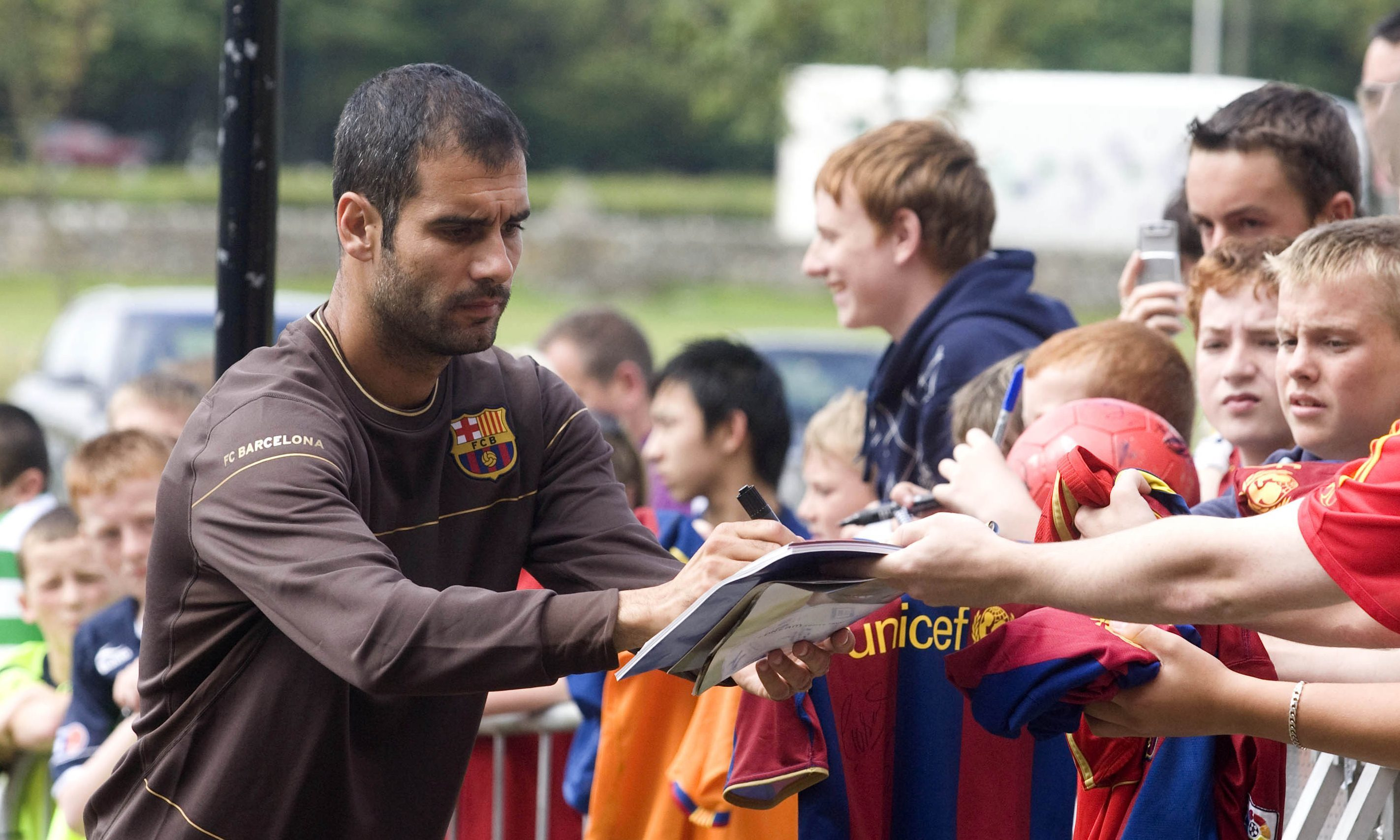 Former Barcelona manager Pep Guardiola signing autographs.