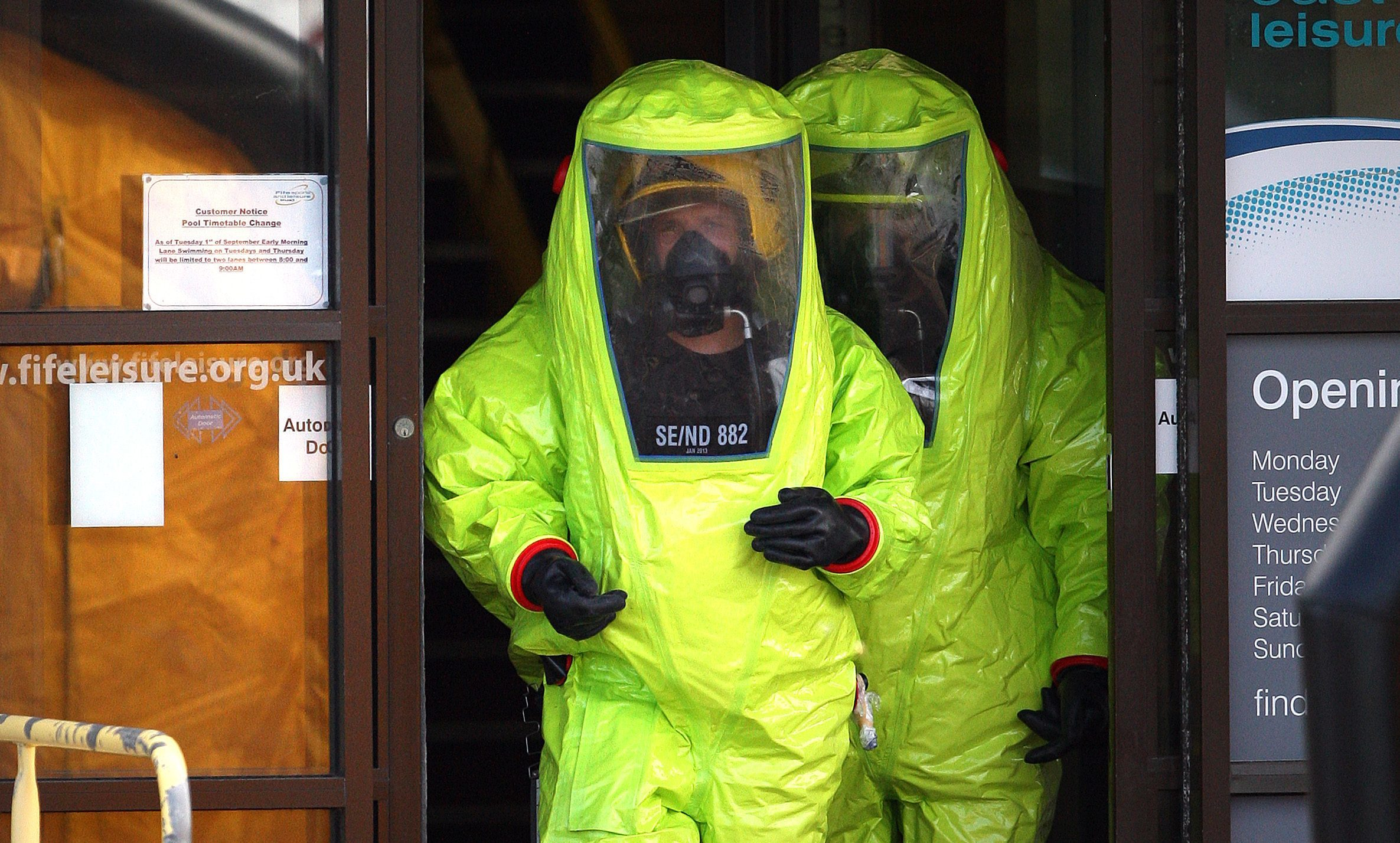 Firefighters in hazmat (hazardous material) suits leaving the leisure centre during the incident.