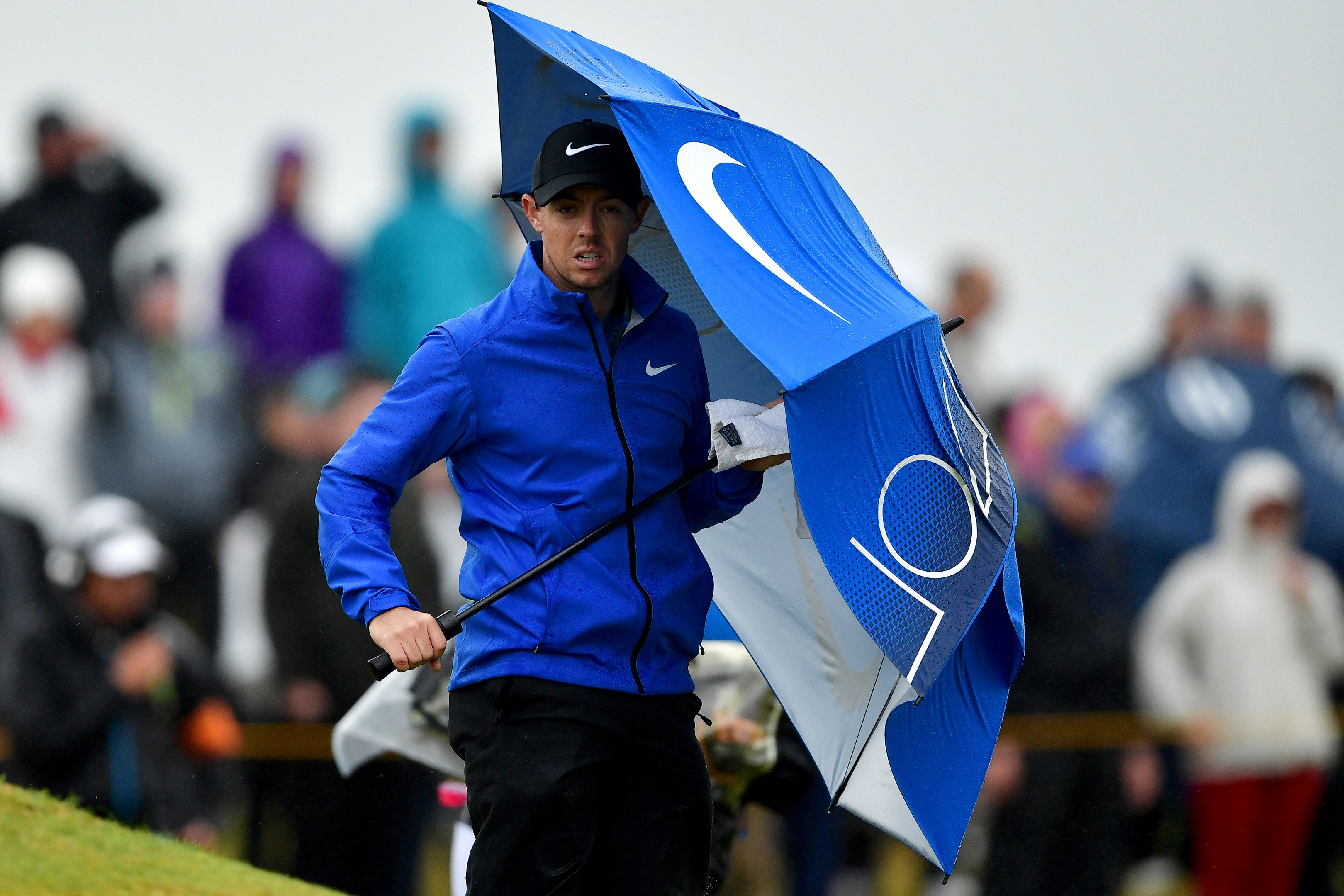 Rory McIlroy takes shelter from the storm during yesterday's second round at Royal Troon.