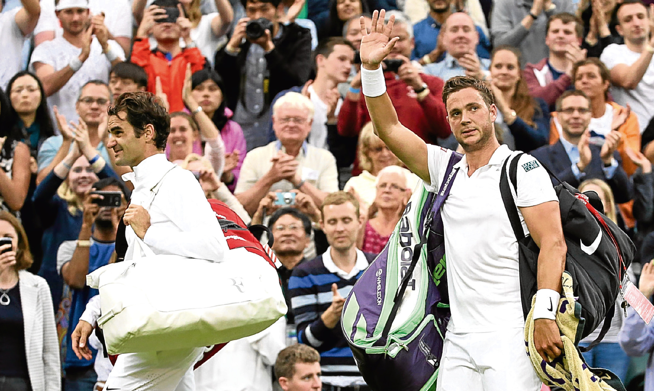 """""""Plucky underdog"""" Marcus Willis waves as he leaves centre court with Roger Federer following defeat at Wimbledon."""