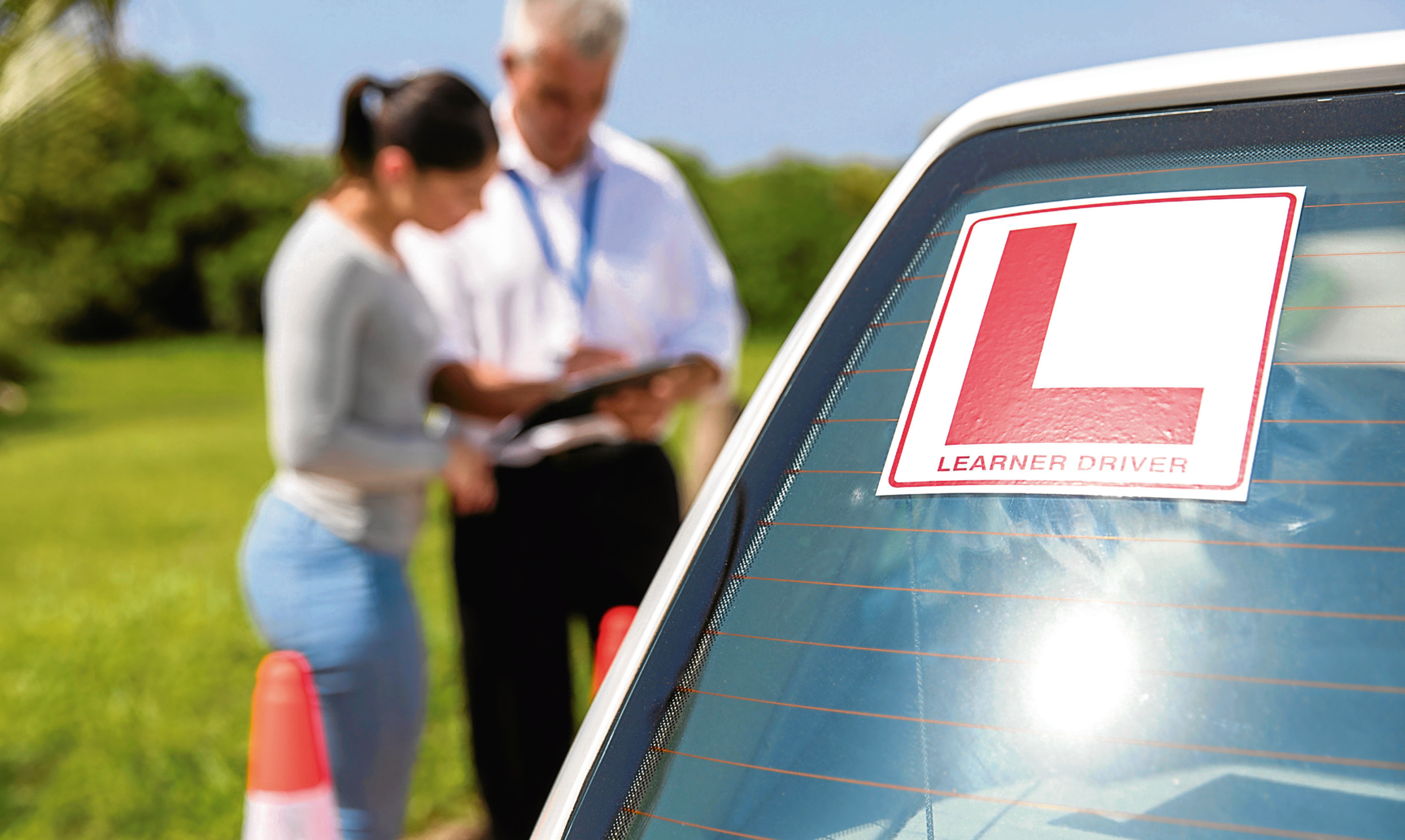 learner driver sign on a car with student and instructor standing behind