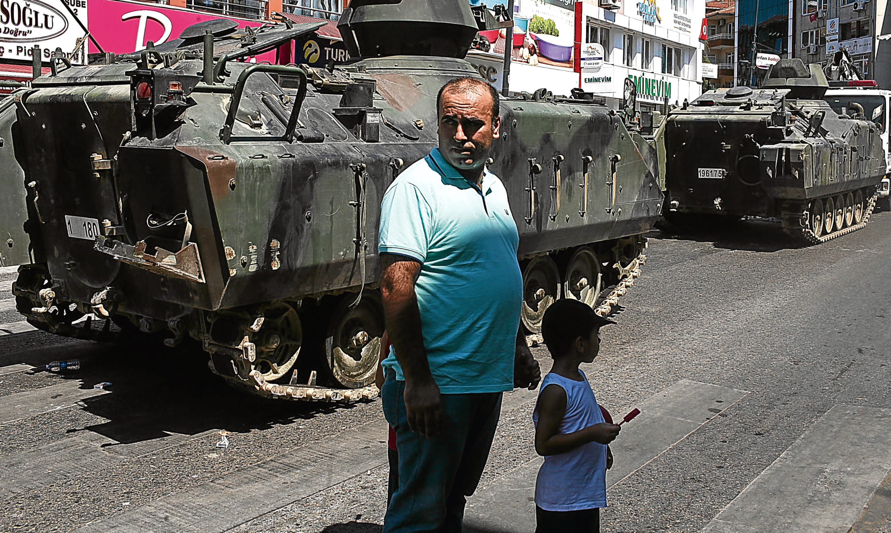 A Turkish man and his son stands near an abandoned armoured vehicle in the Uskudar district of Istanbul.