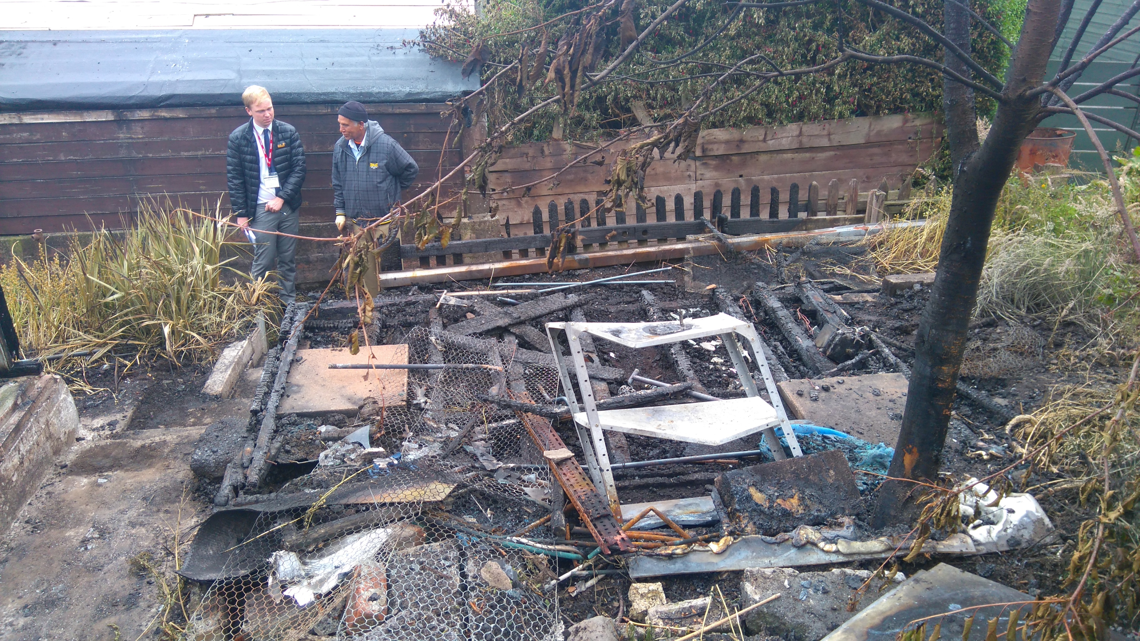 Mr Ahmed inspects the ruins of his son's allotment shed.