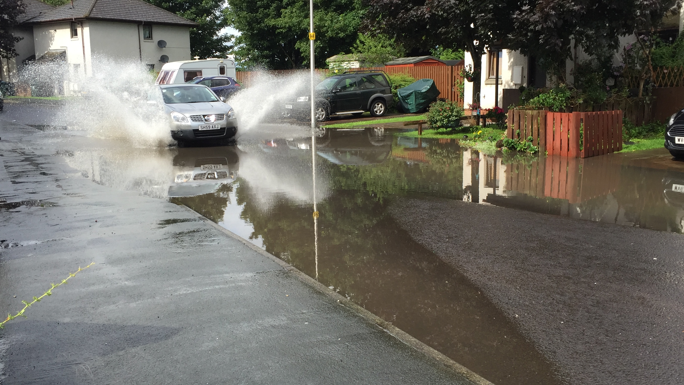 A car drives through the flooding on Cromlix Road.