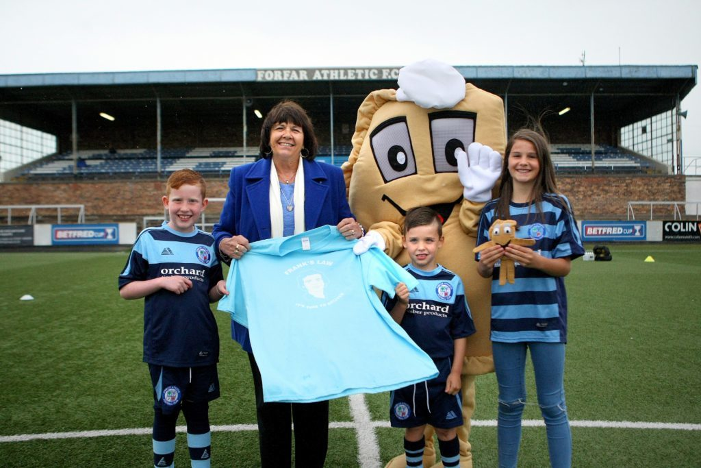 Amanda Kopel presents Baxter the Bridie with a Frank's Law T-shirt while young Forfar Athletic fans look on.