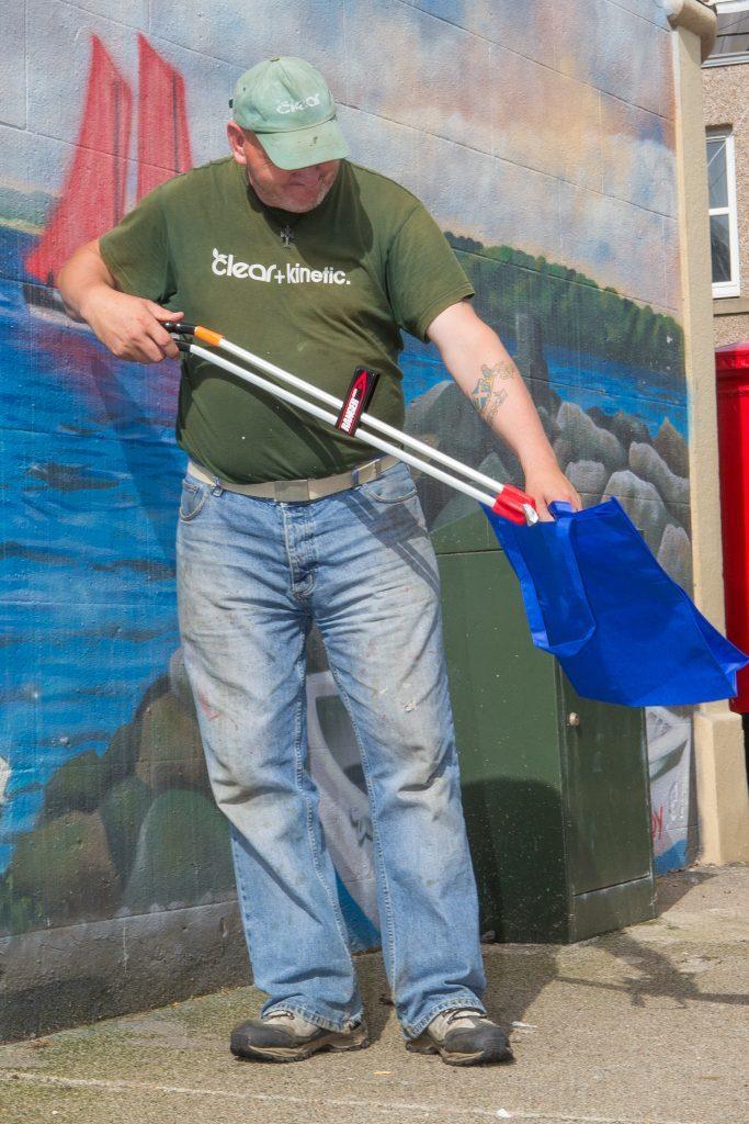 Volunteer Colin Pentland tackles litter on Mitchell Street.