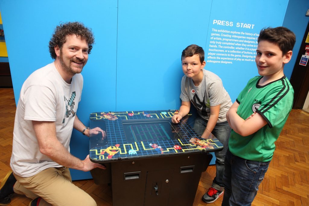 Chris van der Kuyl , at Perth Museum with Bruno Nowrotek and Sam Duncan, play an 80 eras video game