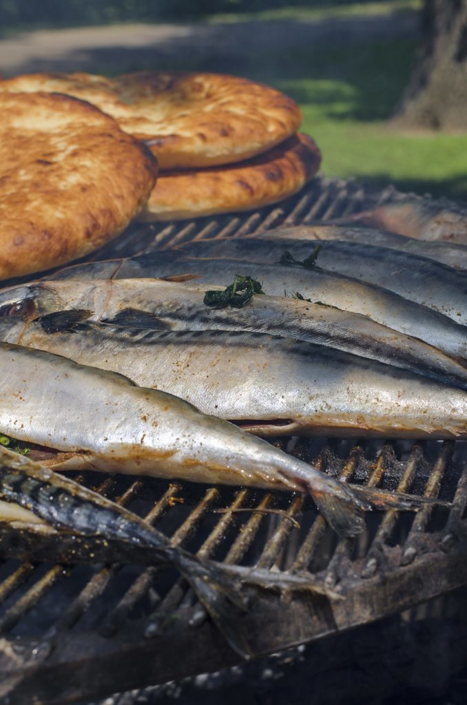 Sea fish (scomber, mackerel) on grill with flatbread on background