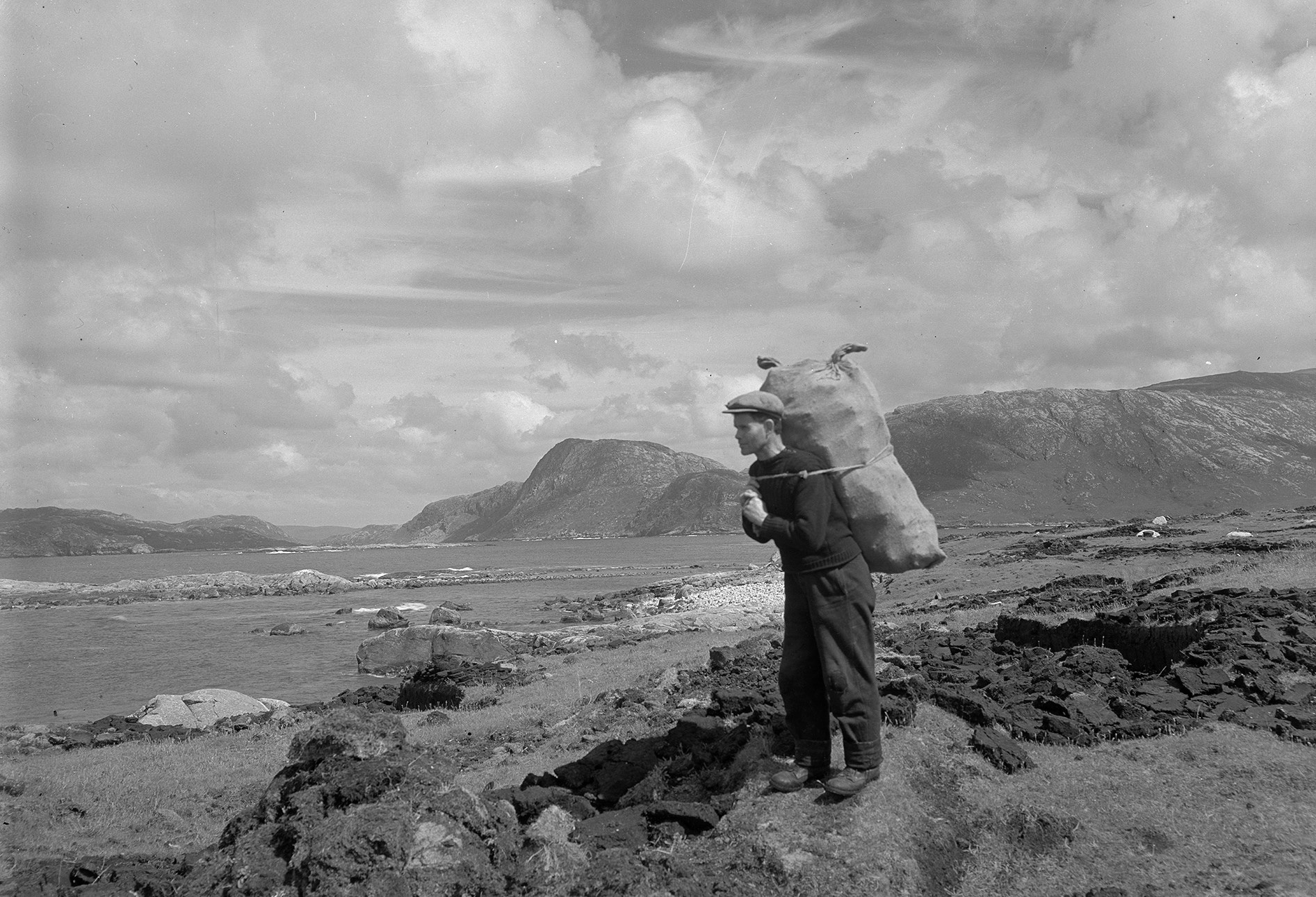 Peatland has been a source of fuel, as well as capturing carbon. Carrying peats, Fladday, Harris, 1937. By Robert Moyes Adam.