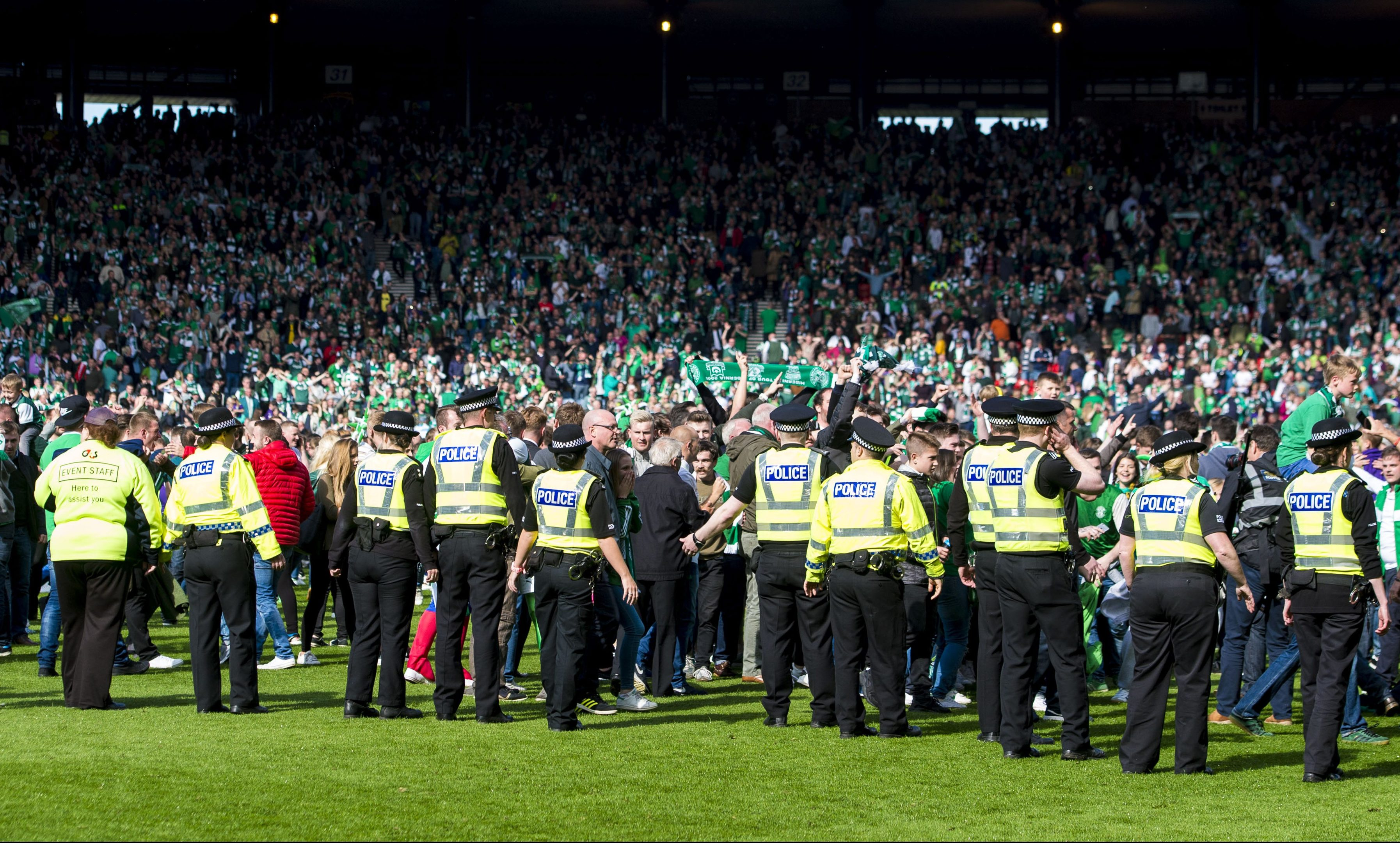 Police work to restore order after fans invaded the pitch at the end of the Scottish Cup final.