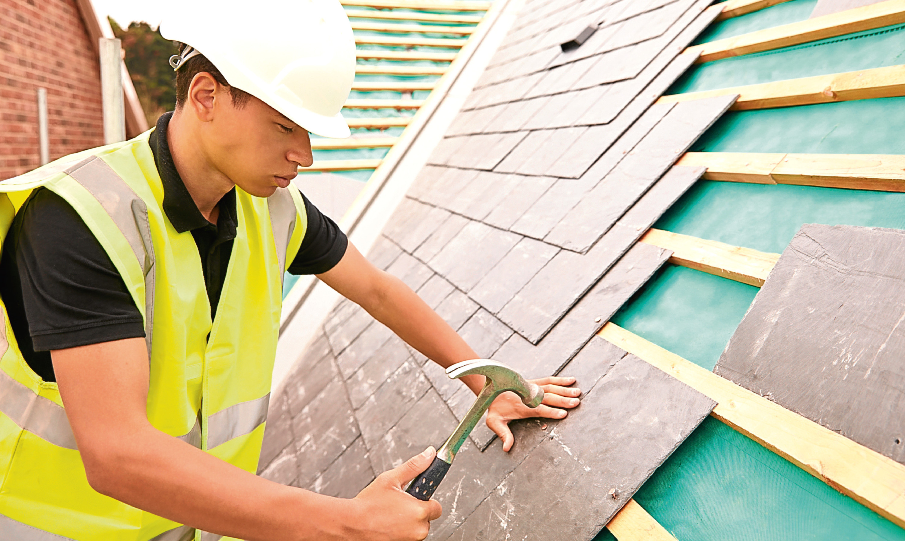 A construction worker lays slate roof tiles