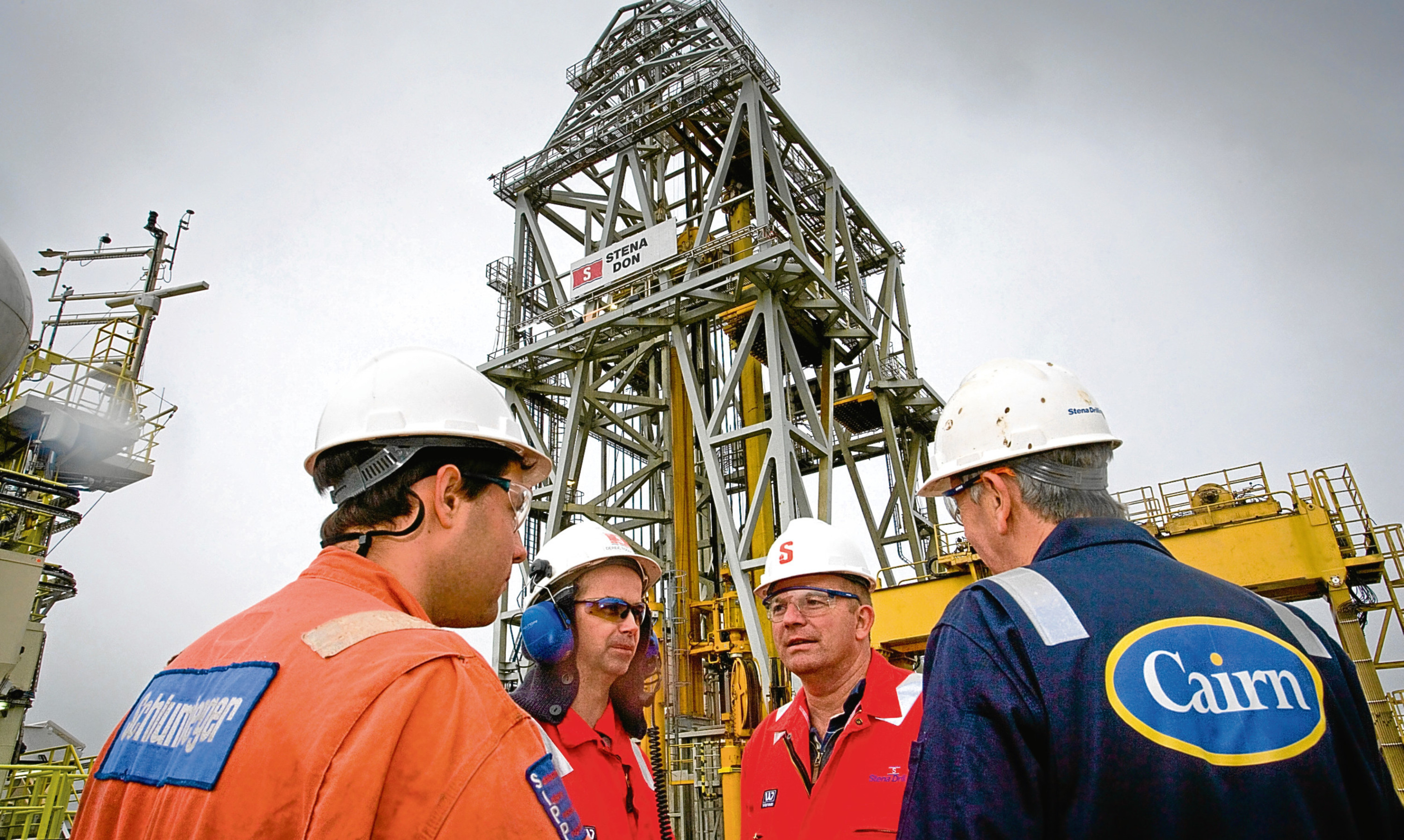 A Cairn technician in discussion with industry colleagues