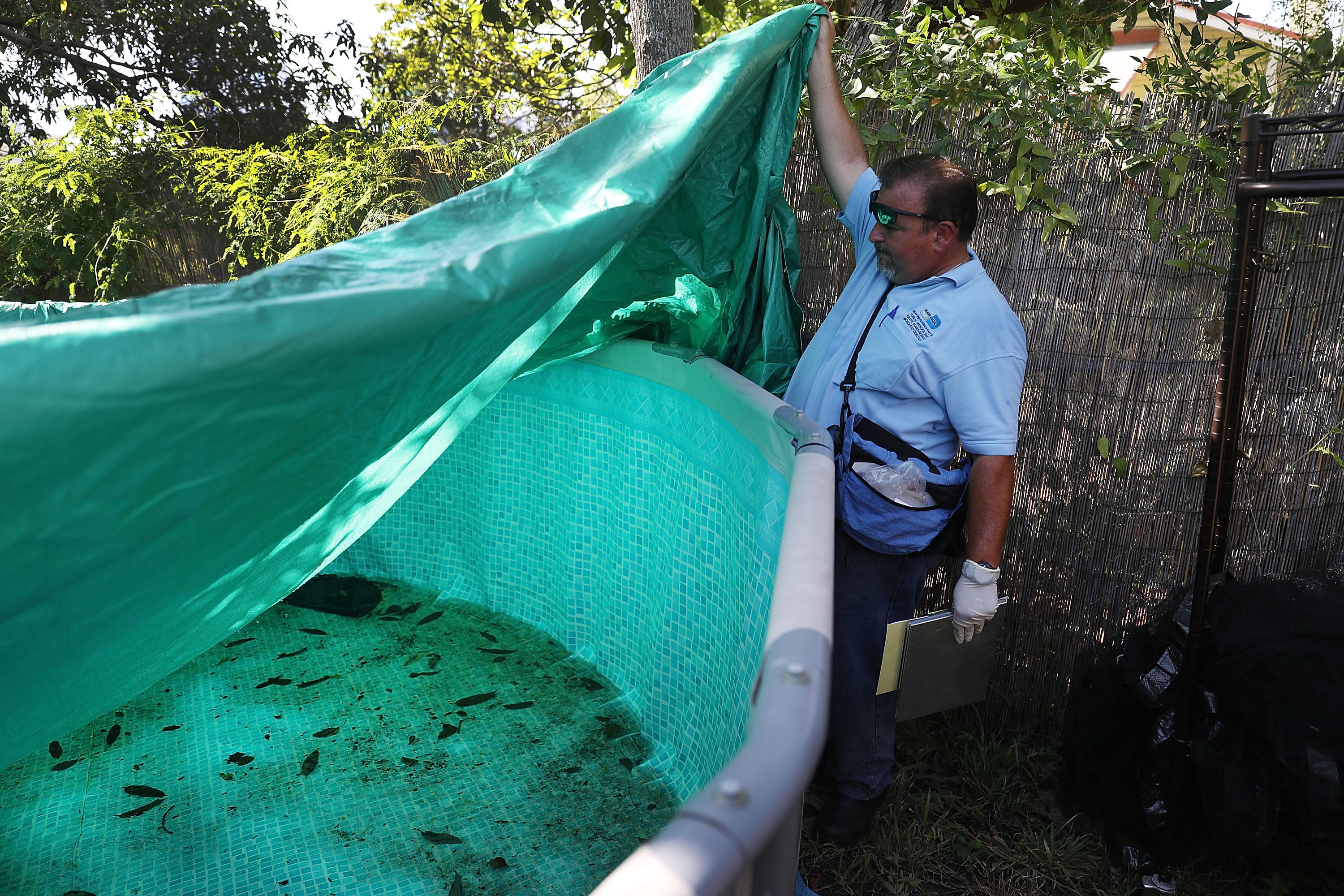 Robert Muxo, a Miami-Dade County mosquito control inspector, inspects a property for mosquitos or breeding areas in the Wynwood neighborhood as the USA fights to control the Zika virus outbreak.