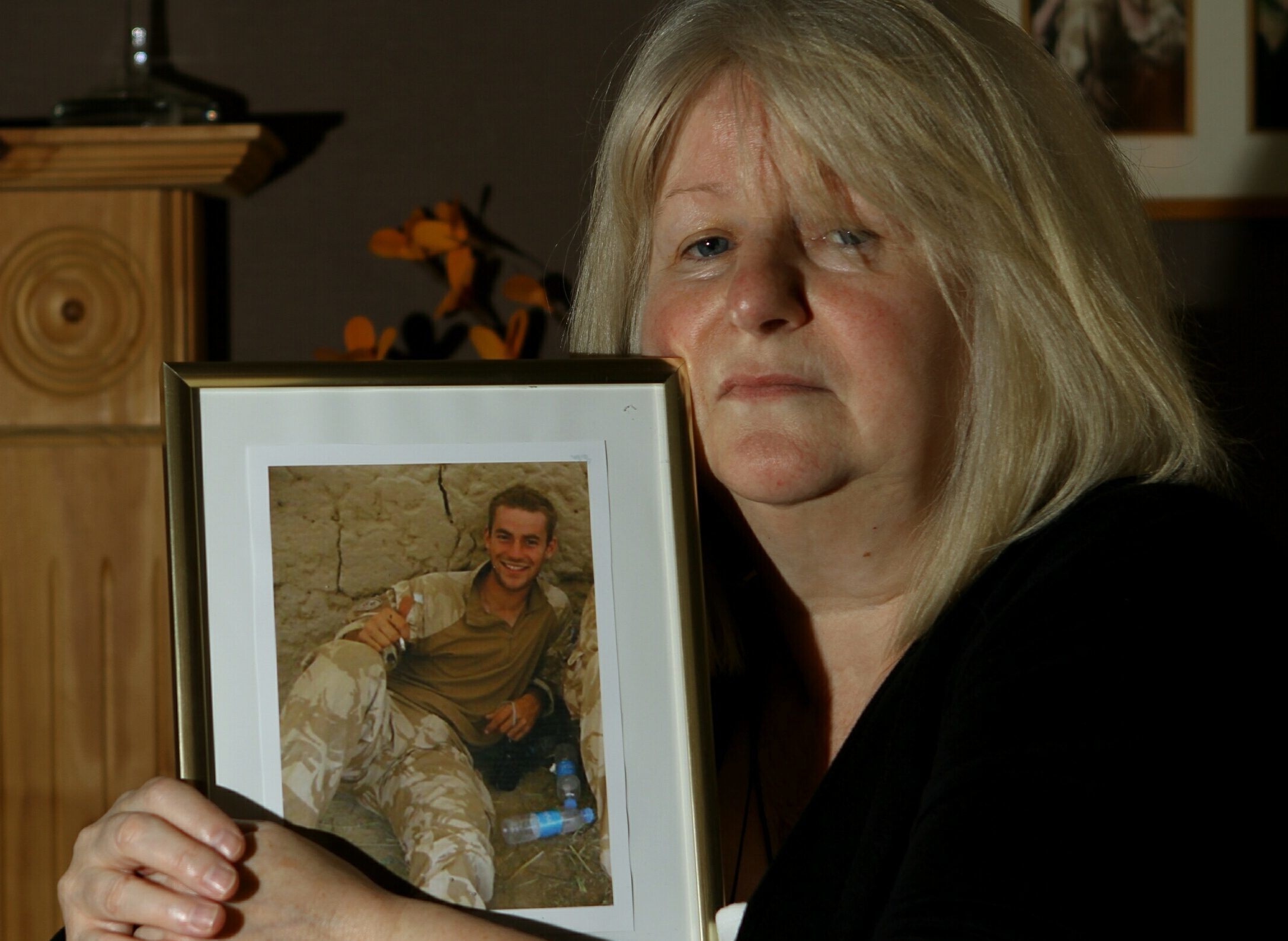 June Black with a photograph of her late son Aaron who committed suicide seven months after coming out of the army