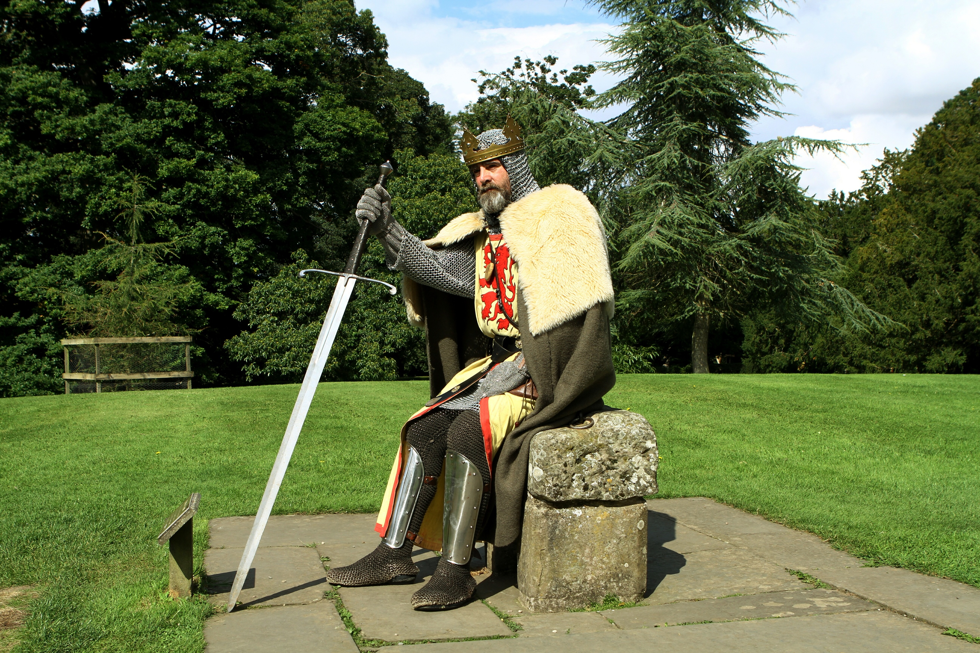 King Robert The Bruce, aka Brian McCutcheon, sitting on a Stone Of Destiny replica.