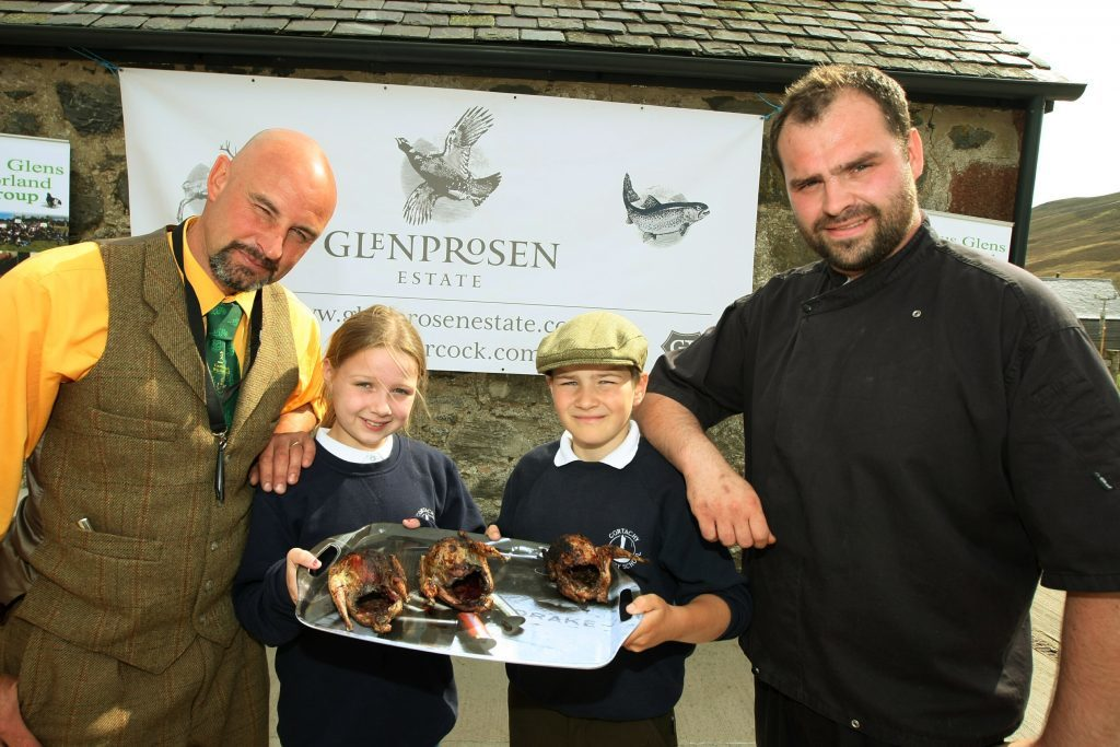 Bruce Cooper and Jordan Sinclair of Sinclair Catering with two pupils and the finished product, a barbecued grouse.