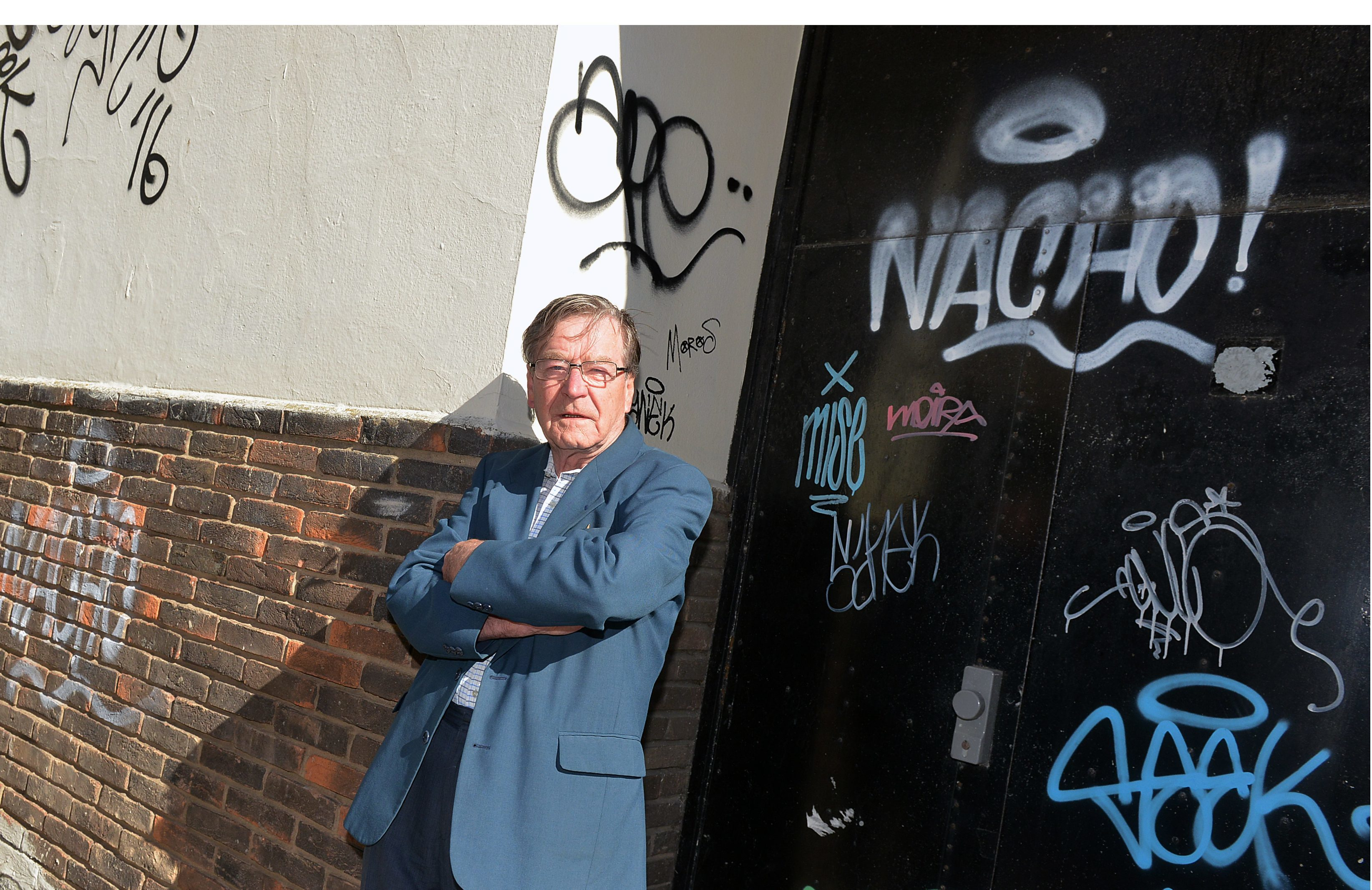 David Henderson, chair of Kirkcaldy West Community Council, next to graffiti in Kirkcaldy town centre.