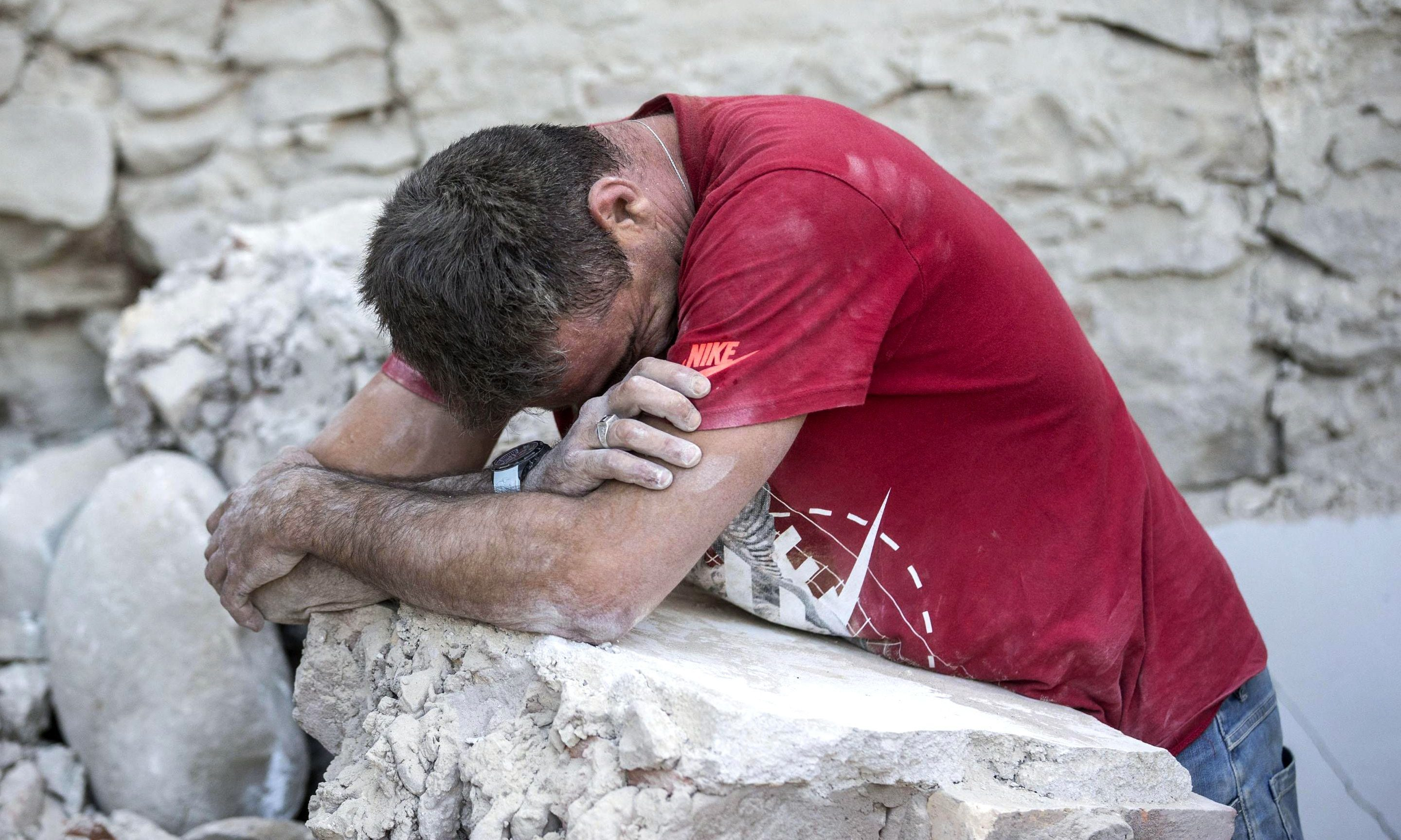 A man leans on rubble in Amatrice as the search continues.